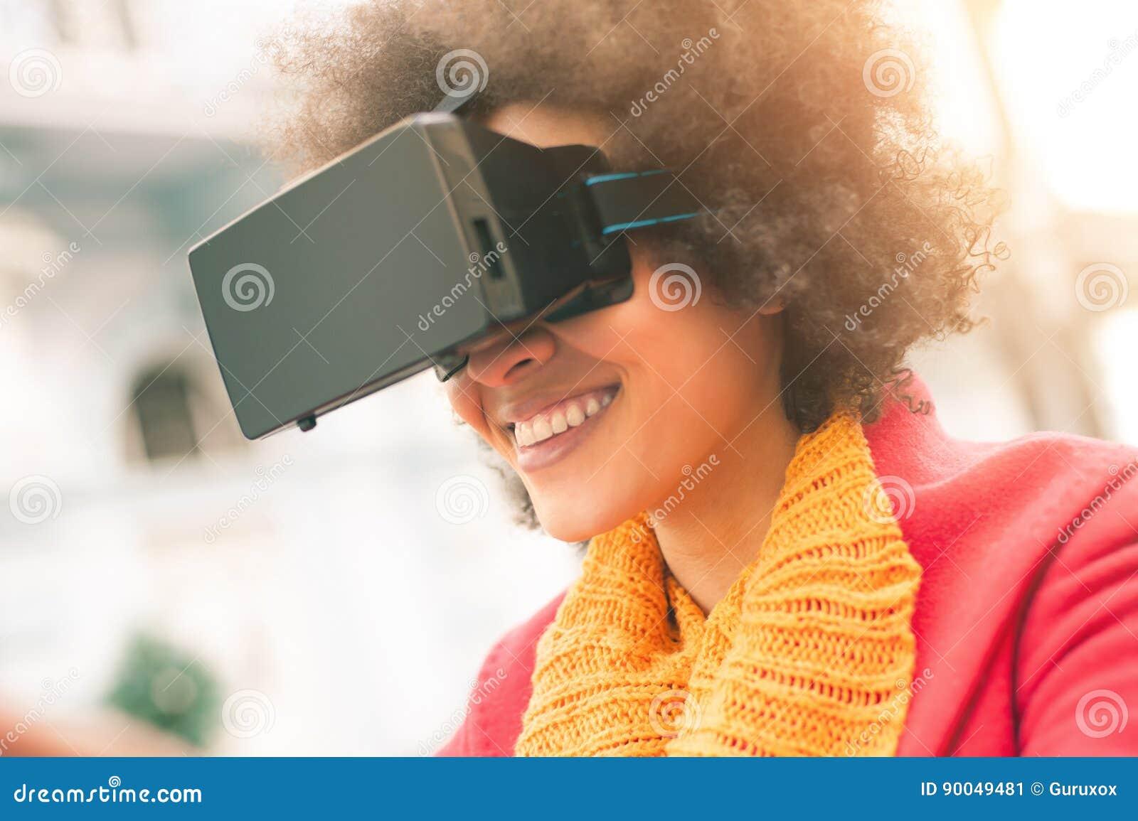 Mulher bonita que usa a elevação - vidros da realidade virtual da tecnologia exteriores