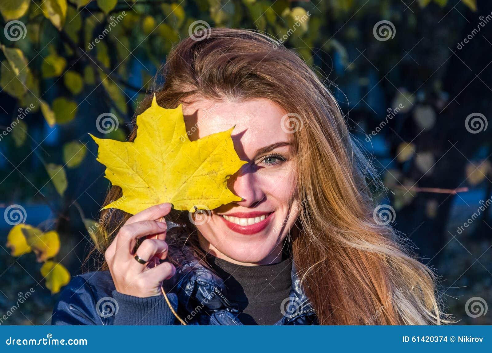 A mulher bonito alegre nova da menina que joga com amarelo caído do outono sae no parque perto da árvore, rindo e sorrindo