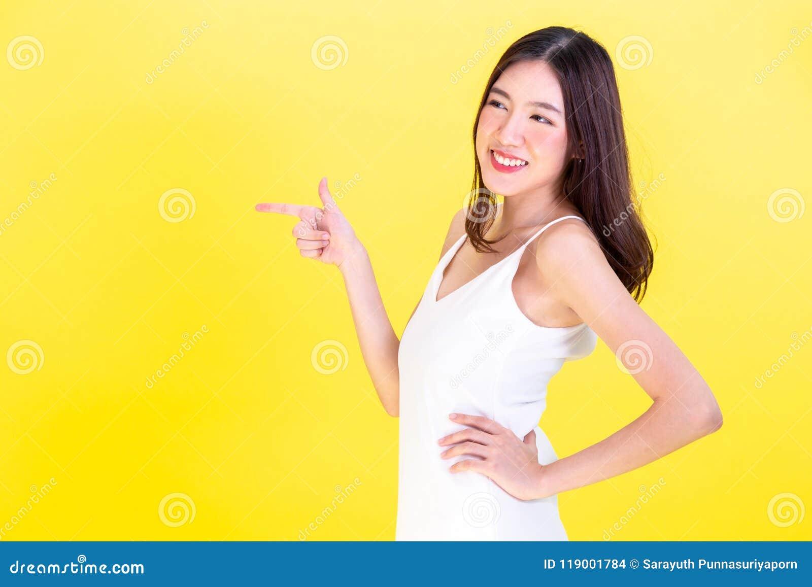 Mulher bonito asiática que aponta as mãos ao espaço vazio da cópia e que levanta os braços akimbo no fundo amarelo