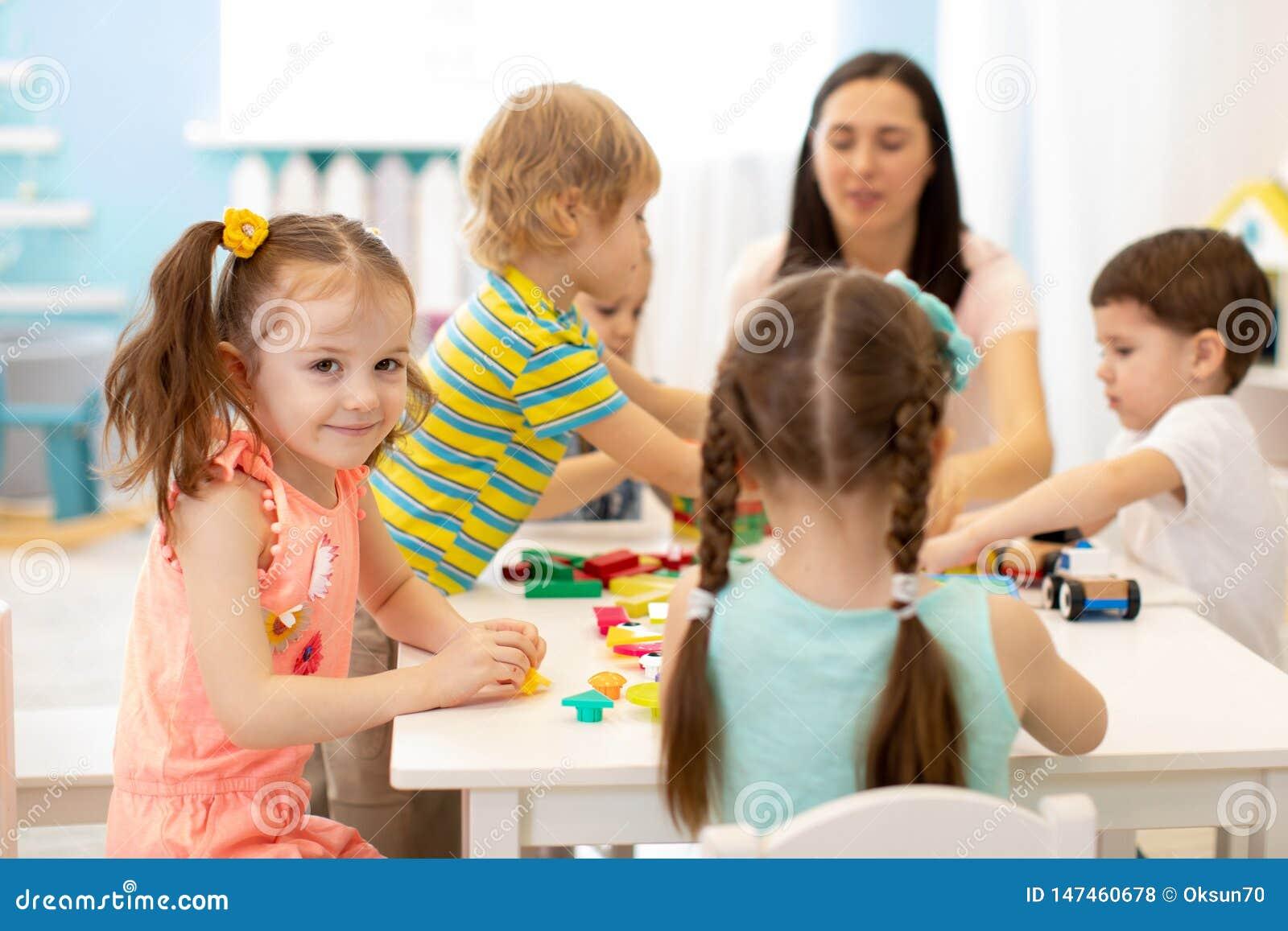 Mulher bonito e crian?as que jogam brinquedos educacionais no jardim de inf?ncia ou na sala do ber??rio