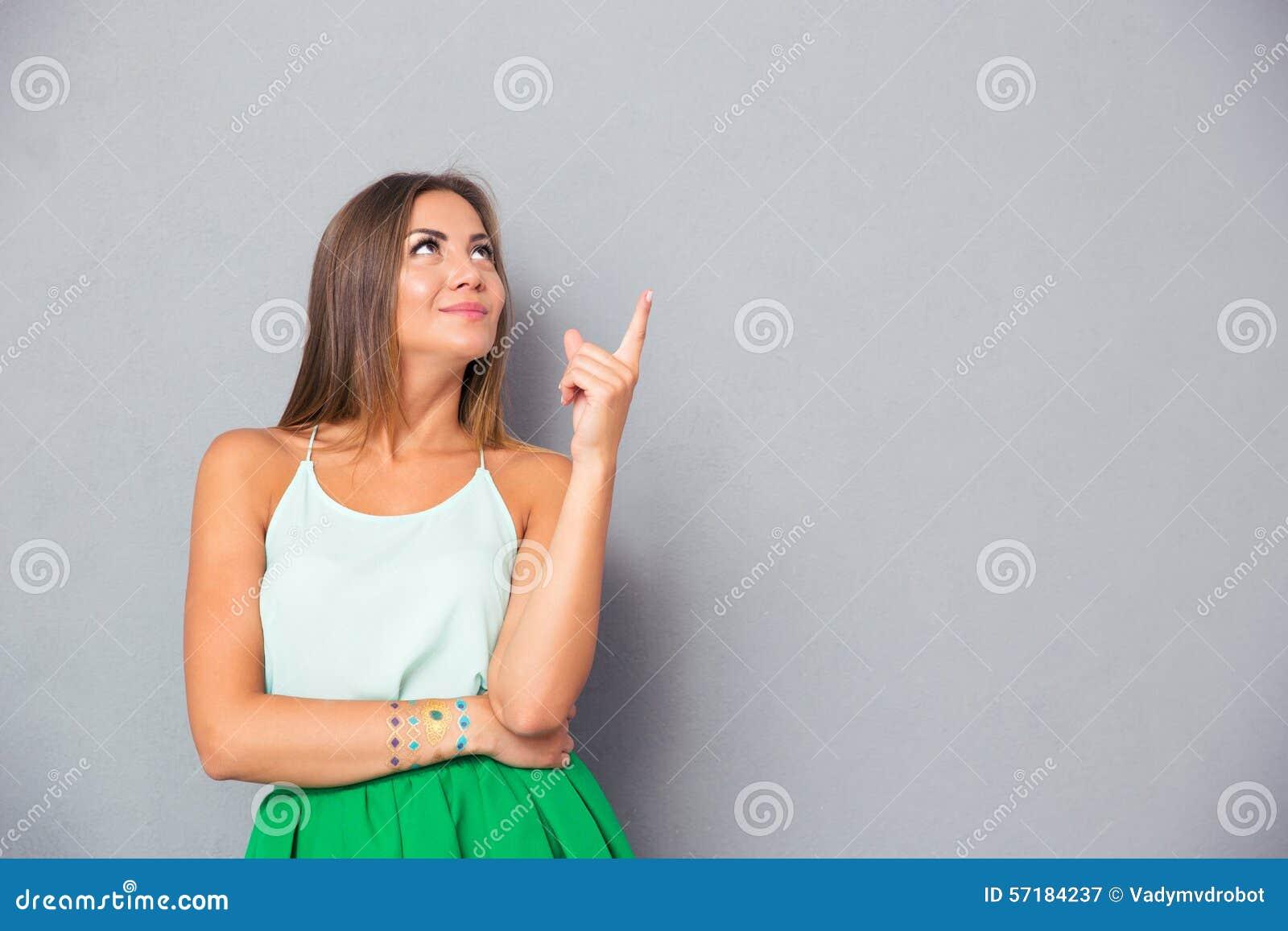 Mulher bonito feliz que aponta o dedo acima