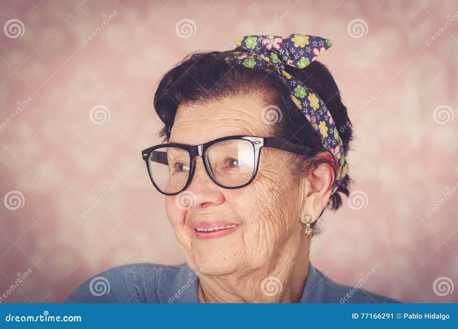 Mulher bonito latino-americano mais idosa com curva do teste padrão de flor em sua cabeça que veste a camiseta azul e grandes vid