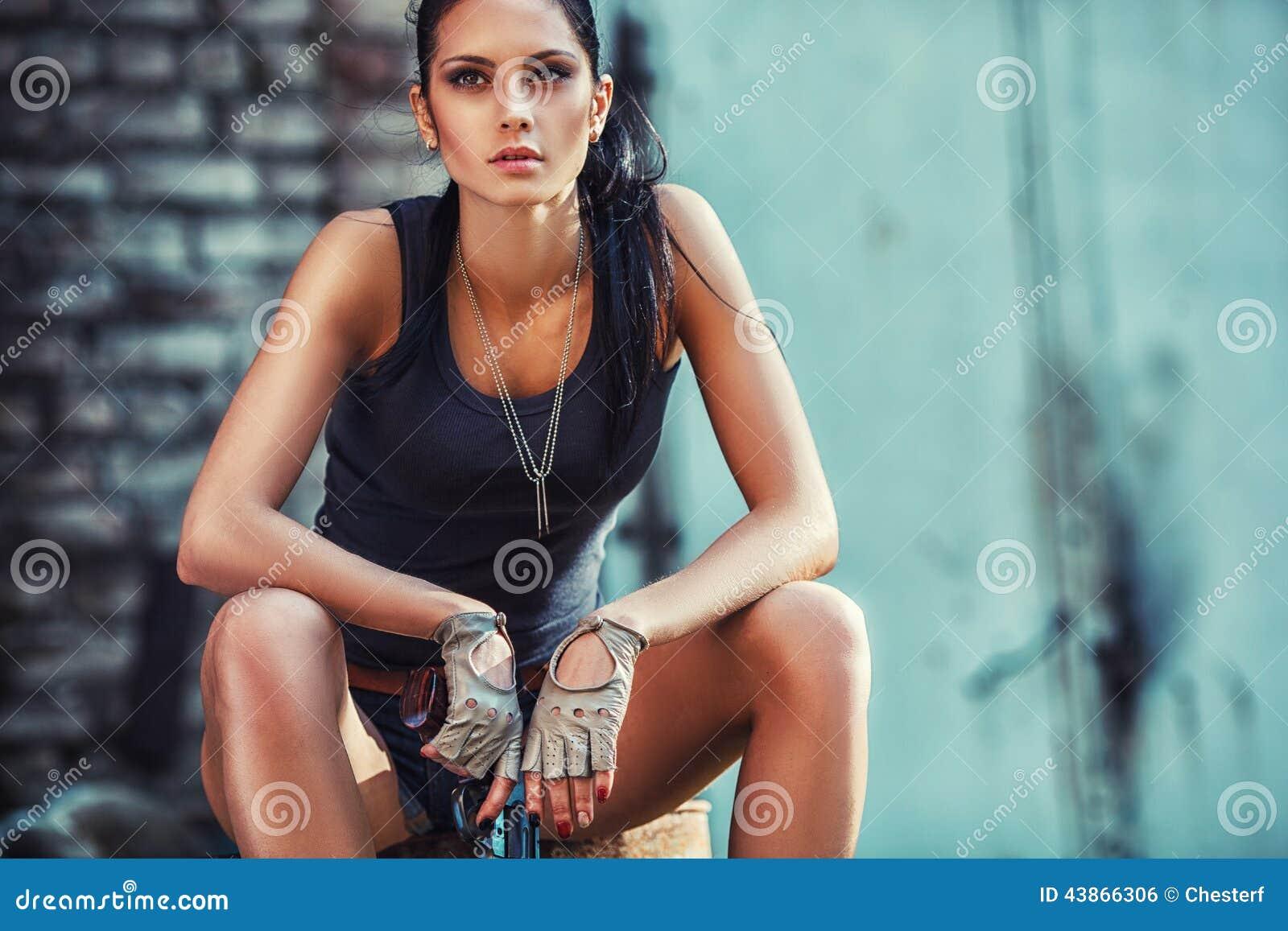 Mulher brutal  sexy  que senta e que guarda o revólver