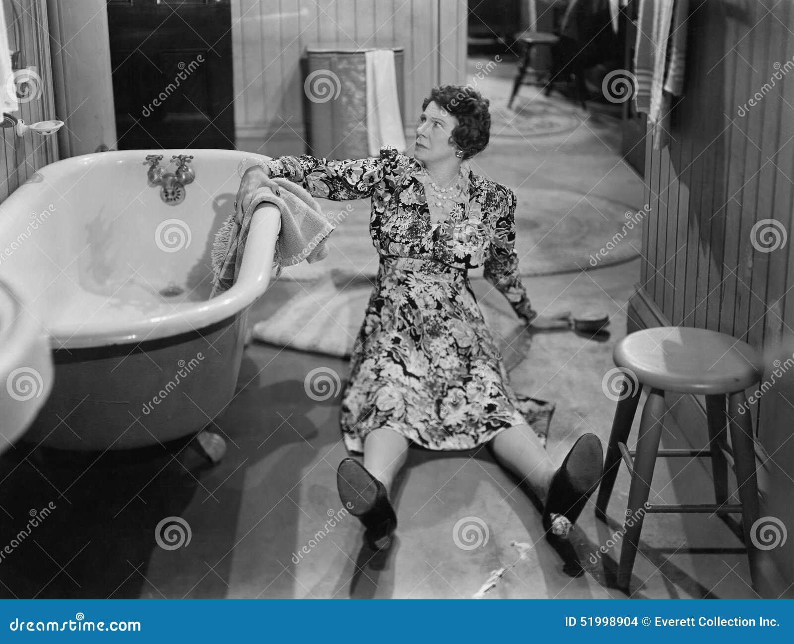 Mulher caída no assoalho ao lado da banheira (todas as pessoas descritas não são umas vivas mais longo e nenhuma propriedade exis