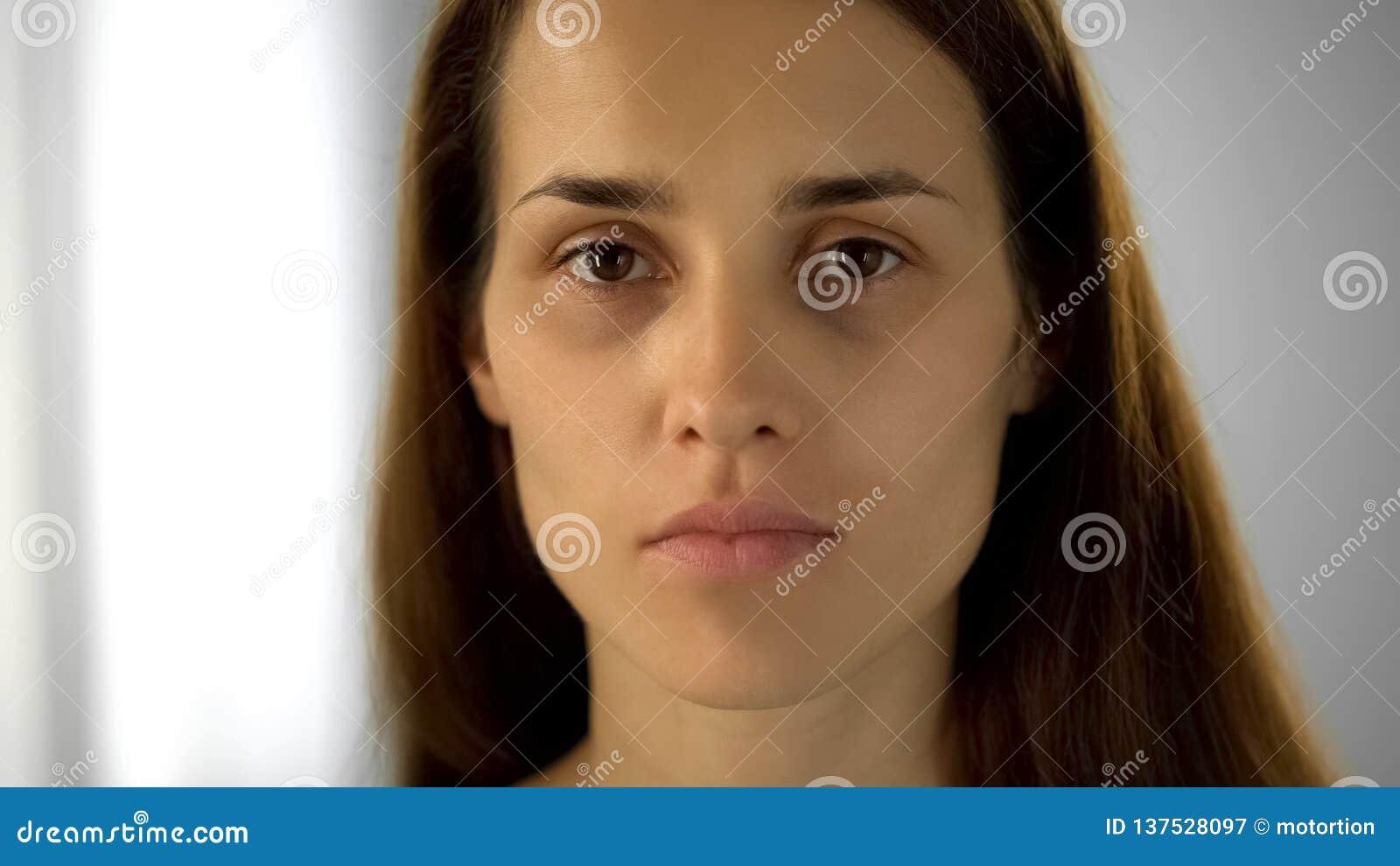 Mulher cansada com círculos pretos sob os olhos que olham a câmera, falta do sono