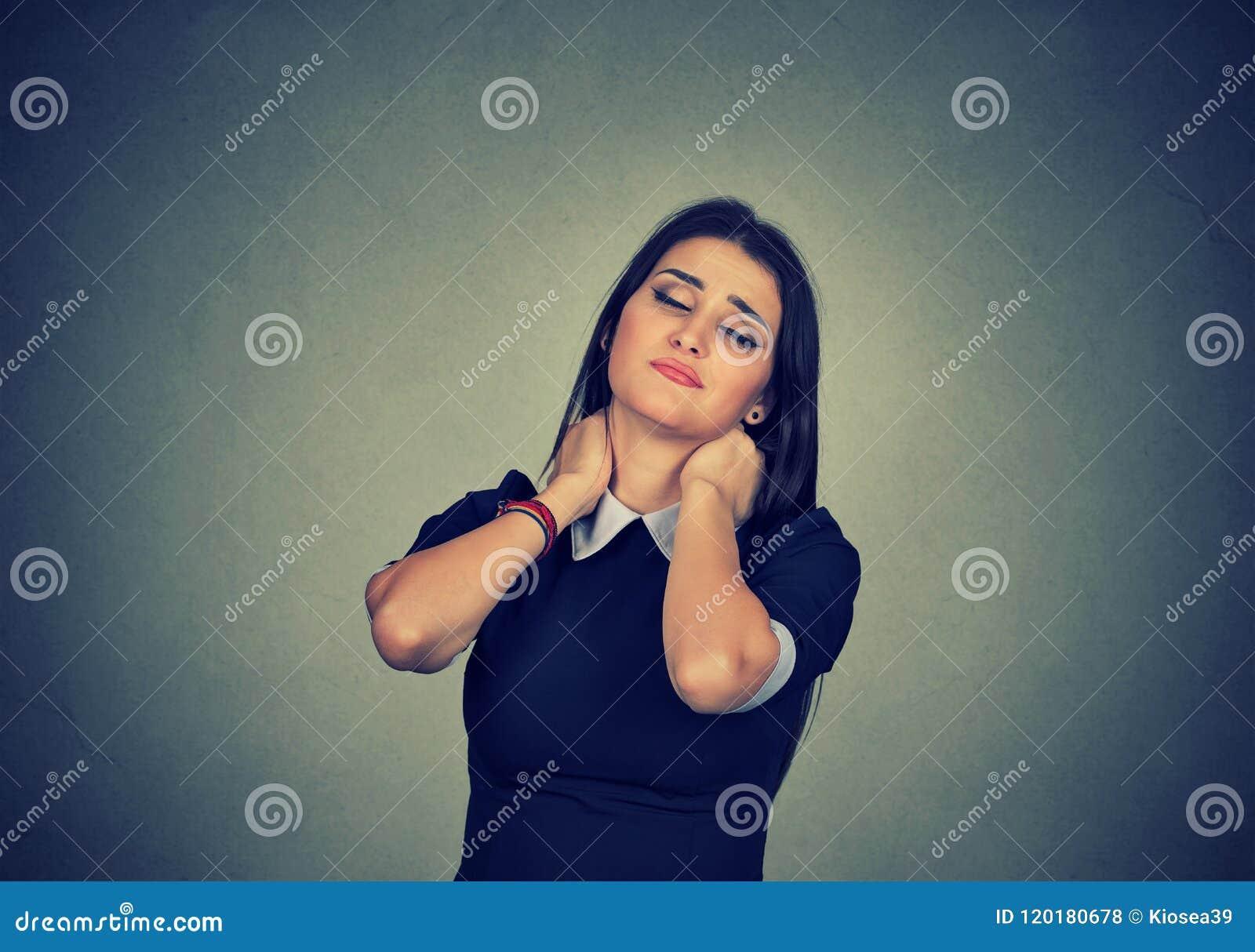Mulher cansado que faz massagens o pescoço esticado