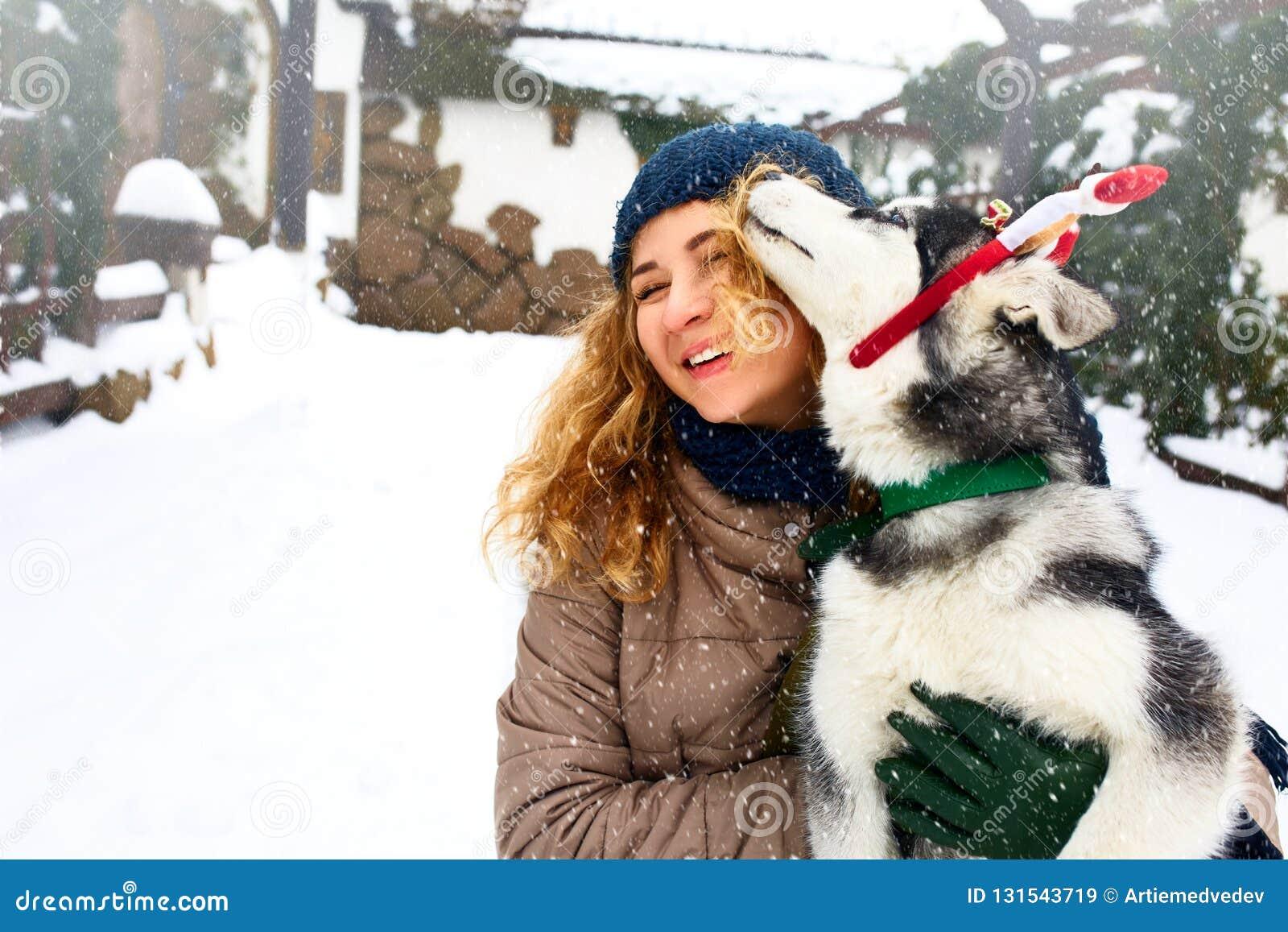 A mulher caucasiano atrativa abraça o cão engraçado do malamute que veste chifres do Natal de Santa os caros Fêmea de sorriso enc