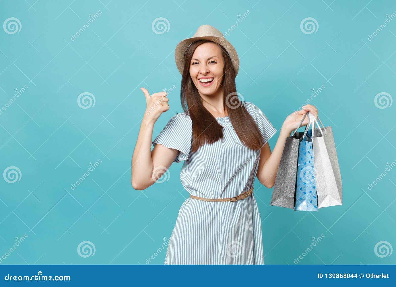 Mulher caucasiano bonita de sorriso elegante do retrato no vestido do verão, chapéu de palha que guarda sacos dos pacotes com com