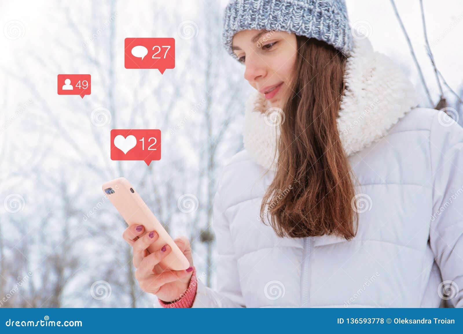 A mulher caucasiano da menina guarda o instagram que do telefone os seguidores sociais do ícone do bloger dos meios gostam do con