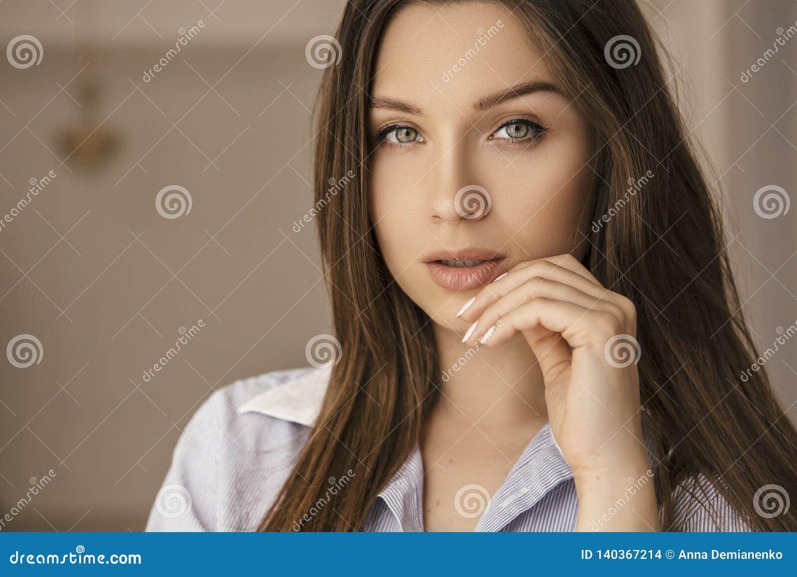Mulher caucasiano moreno apta na camisa dos homens em casa Cara sem falhas bonita Levanta sensualmente E