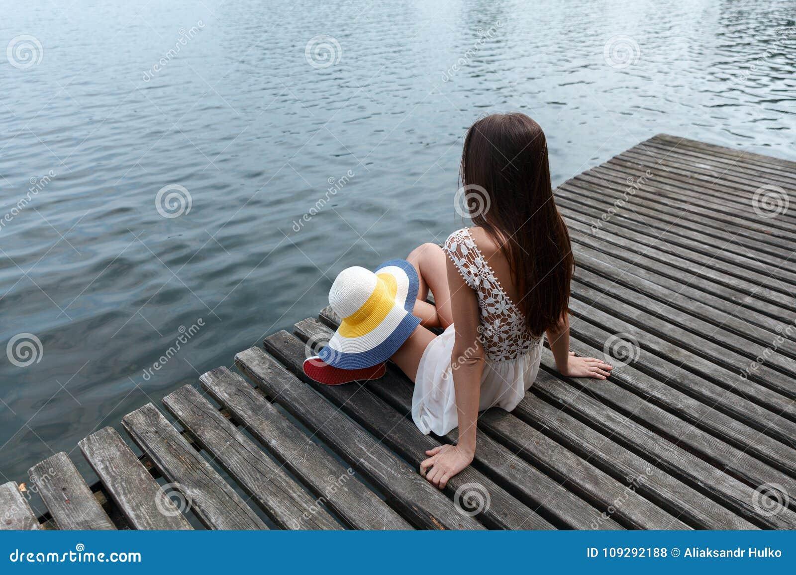 Mulher caucasiano moreno que senta-se apenas em uma ponte em um vestido branco curto