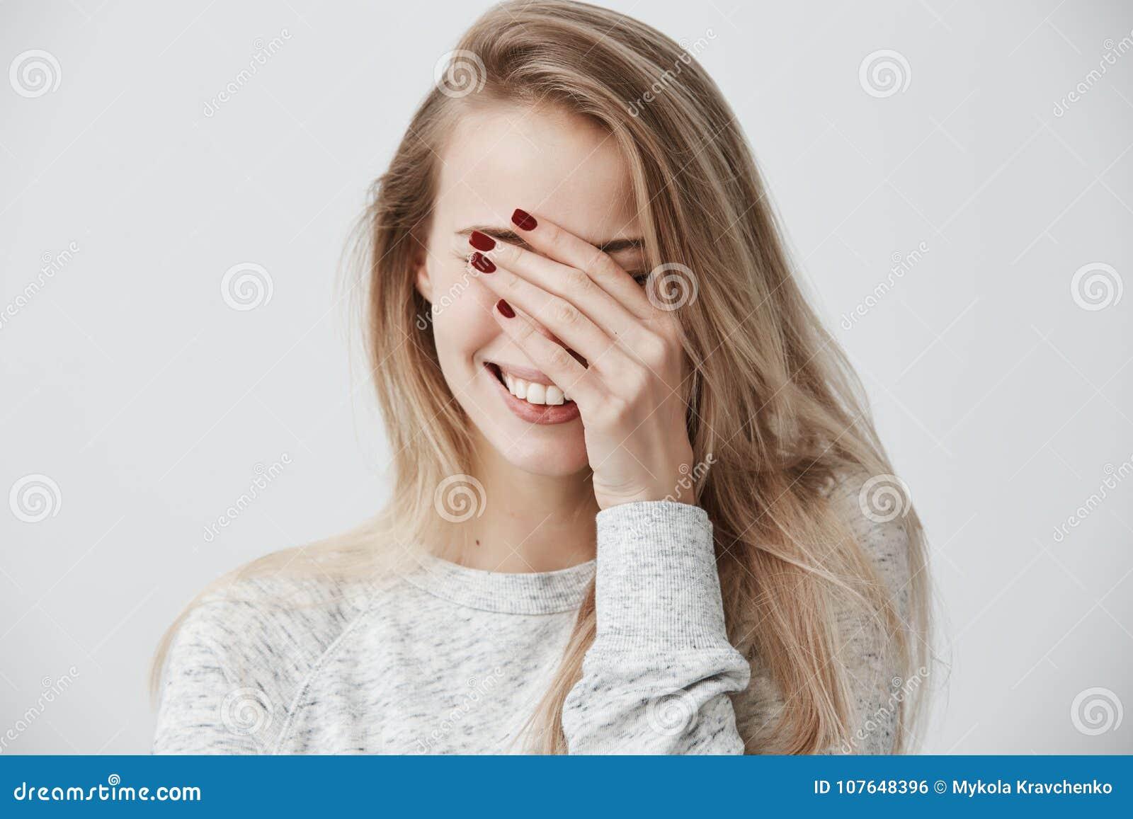A mulher caucasiano nova emocional bonita com o cabelo longo louro, fechando-se eyes com mão ao rir para fora ruidosamente