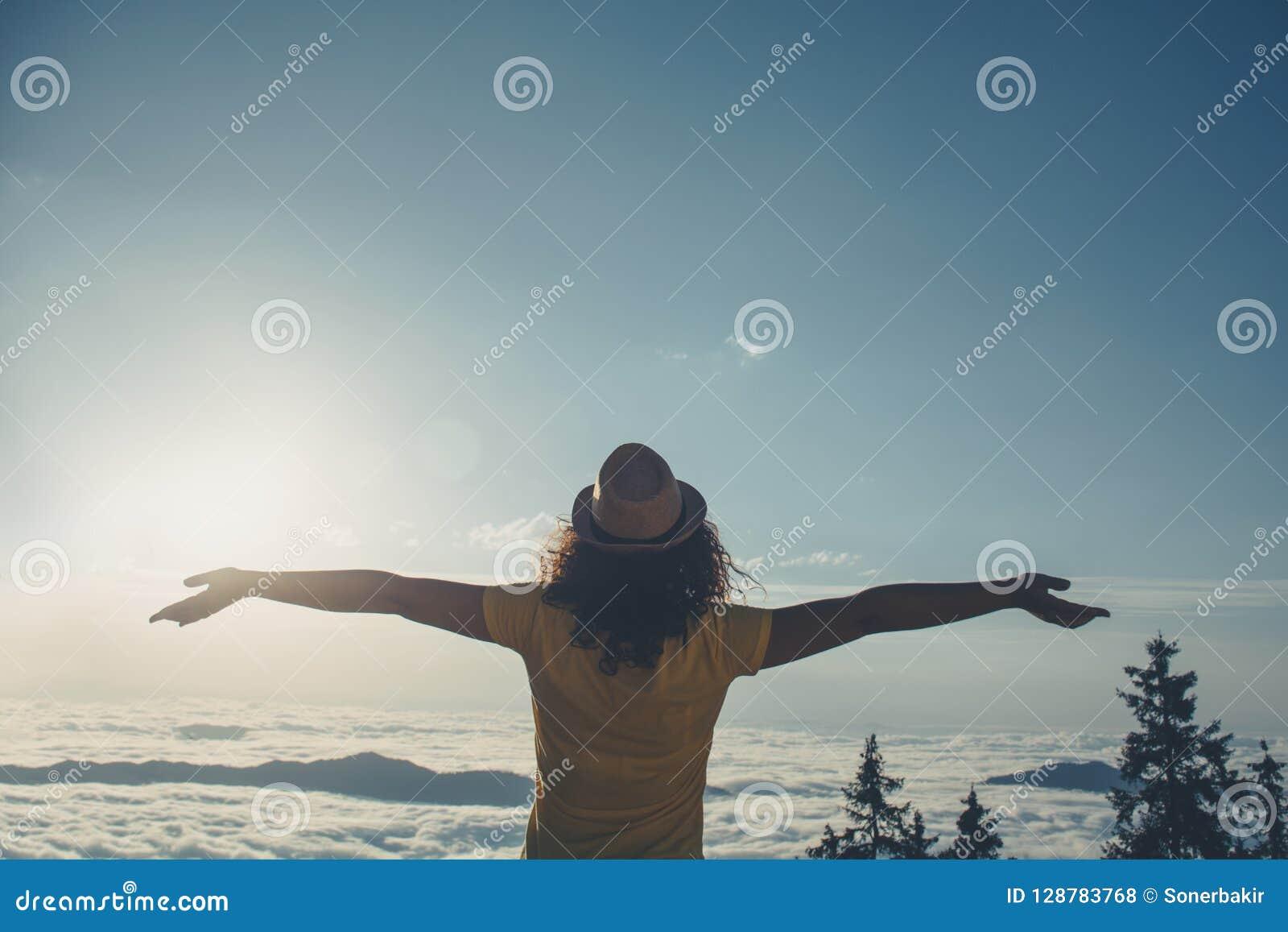 A mulher Cheering aprecia a vista bonita no pico de montanha