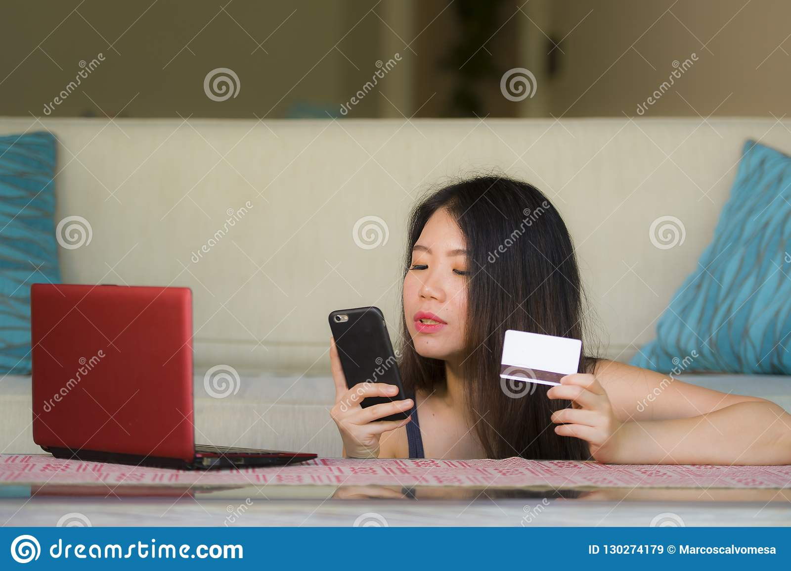 Mulher chinesa asiática feliz e bonita nova que guarda o cartão de crédito usando o telefone celular para Internet banking e o sm