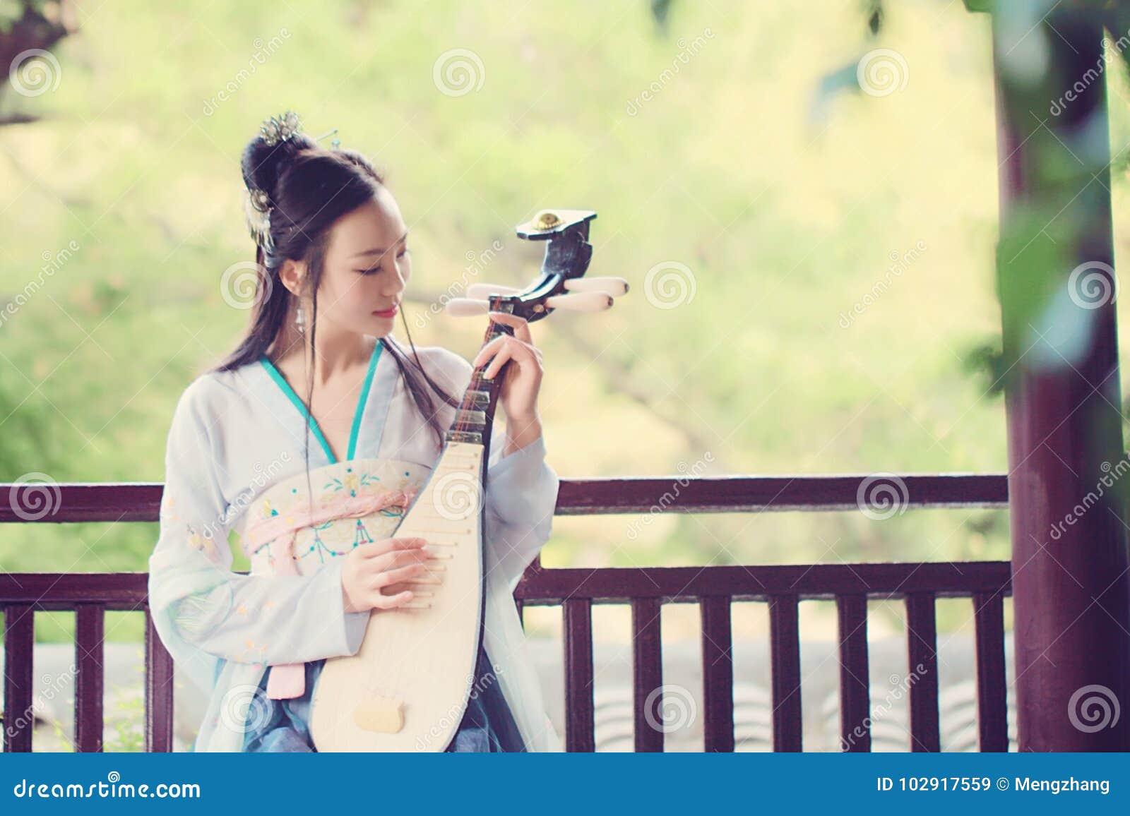 A mulher chinesa no vestido tradicional de Hanfu, joga o instrumento tradicional do pipa