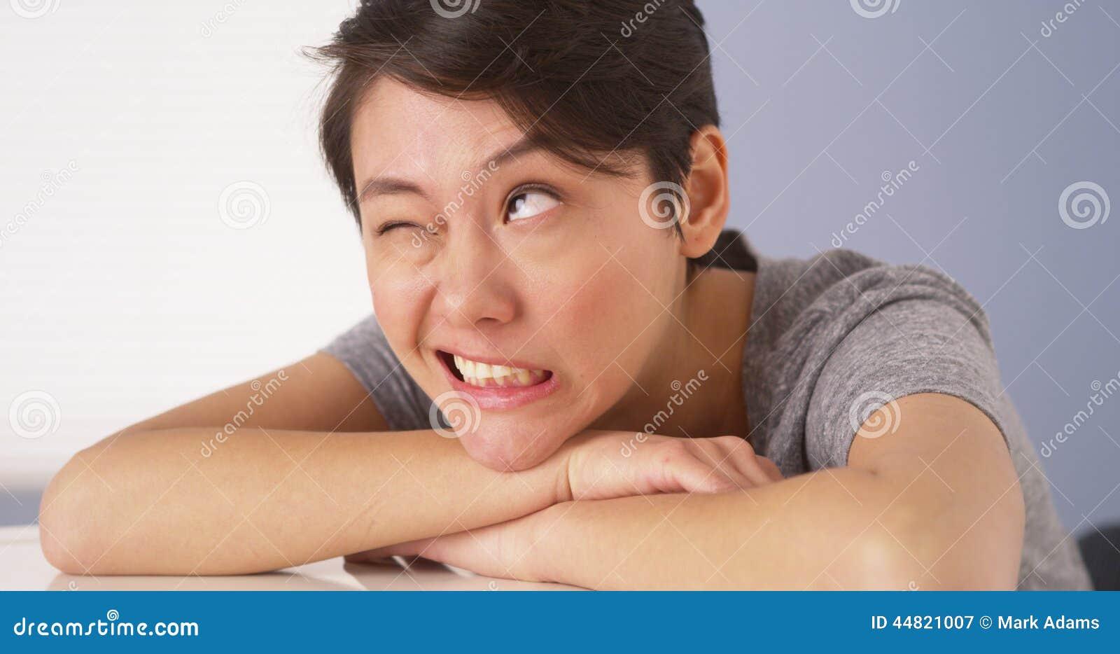 Mulher chinesa que faz as caras parvas na câmera