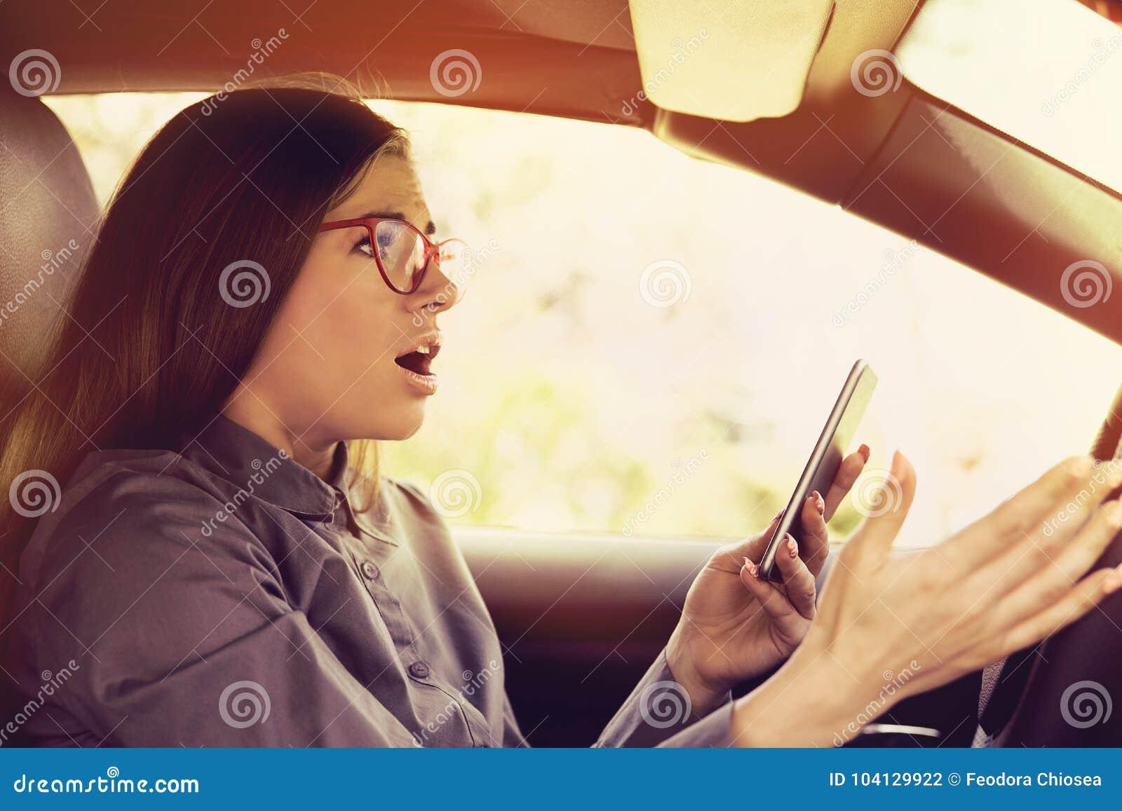 Mulher chocada confundida pelo telefone celular que texting ao conduzir um carro