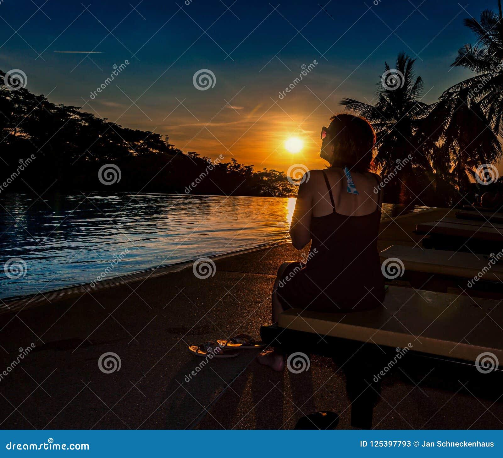 A mulher com óculos de sol olha no por do sol