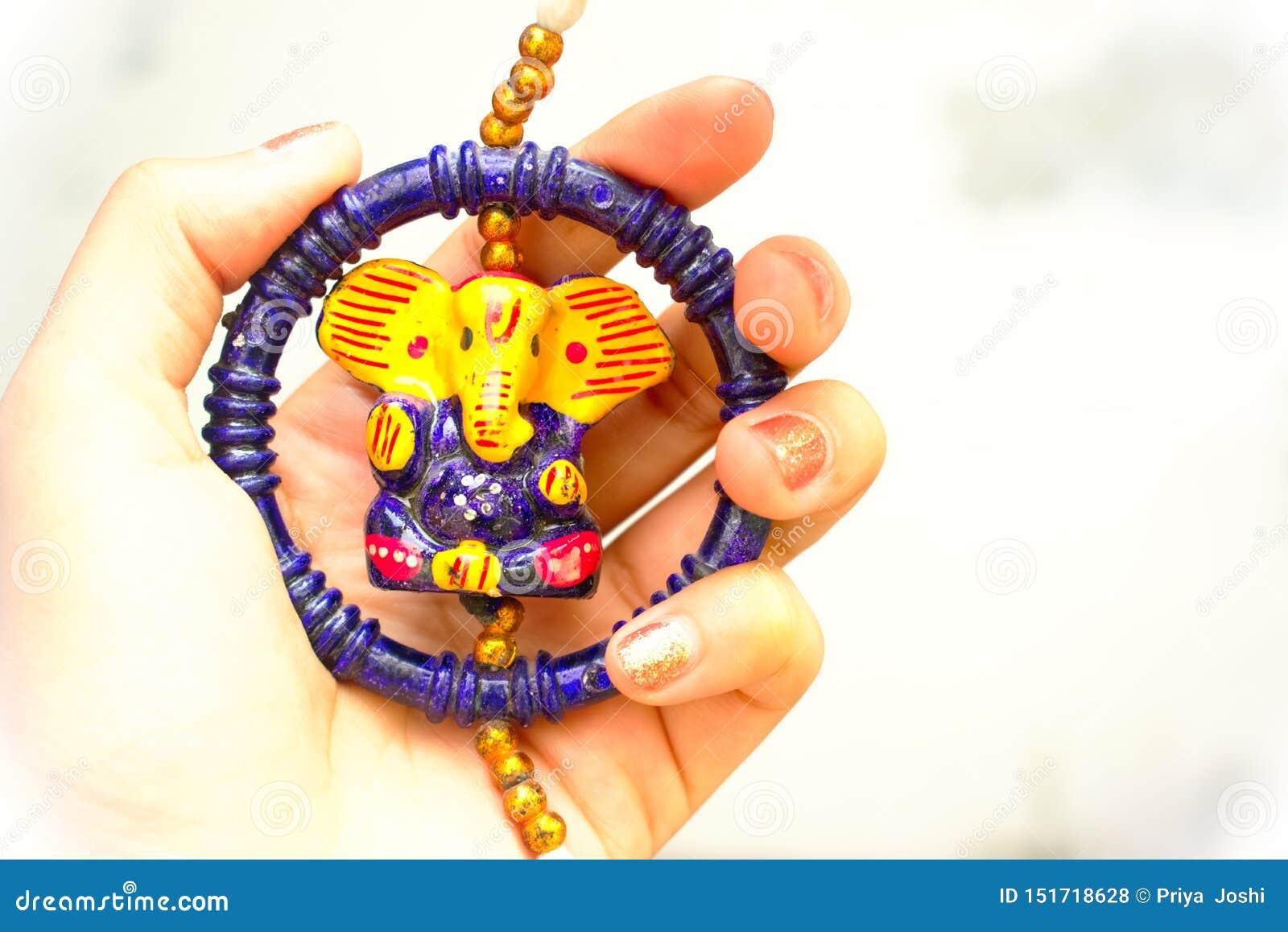 Mulher com as mãos bonitas que guardam o ídolo colorido bonito do ganesha indiano do senhor do deus vendido geralmente durante o