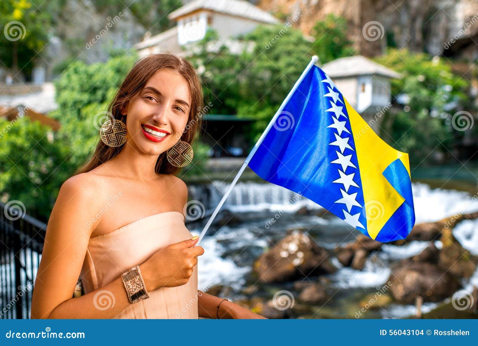 Mulher com a bandeira bosniana na vila de Blagaj