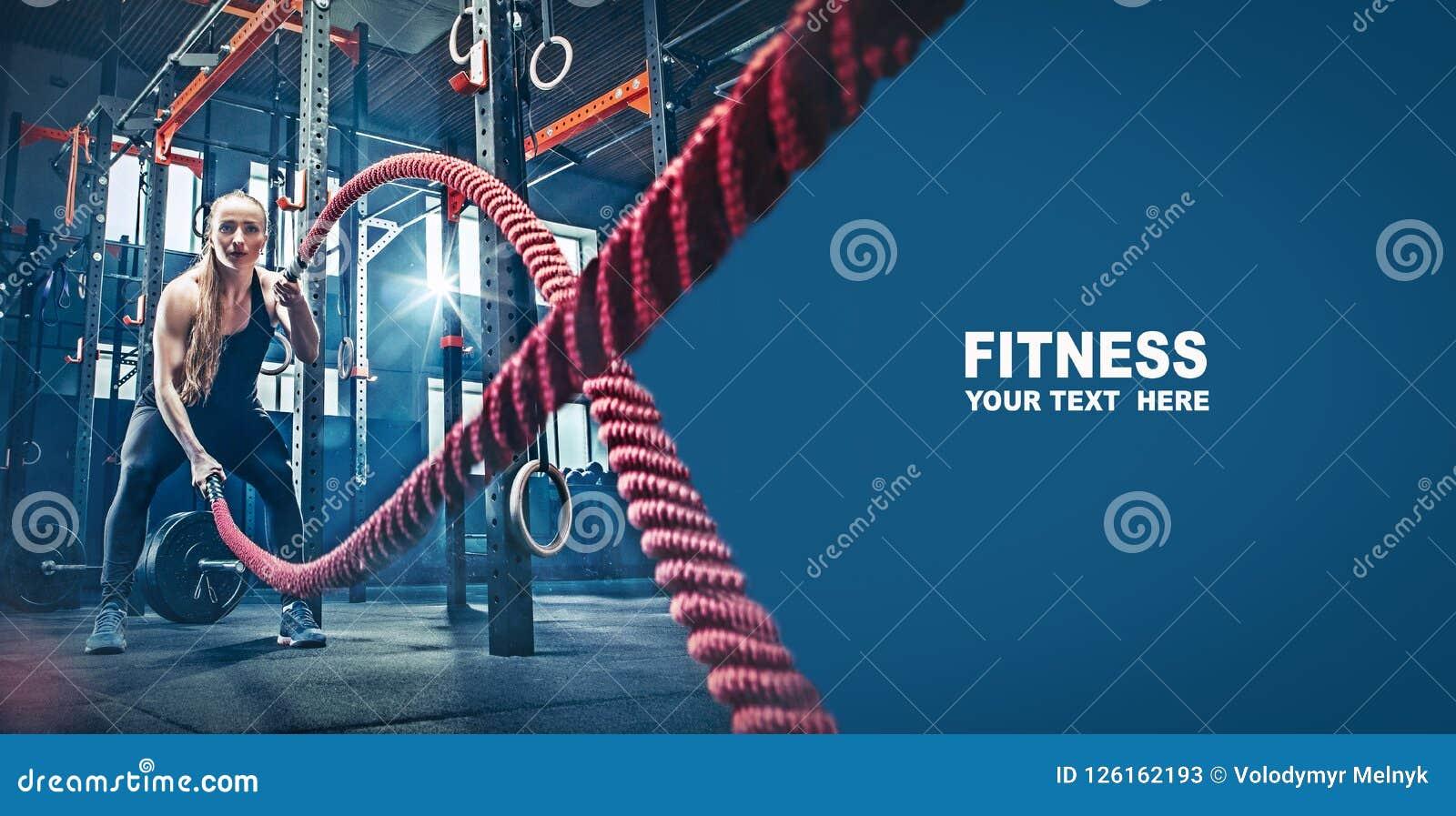 A mulher com batalha da corda da batalha ropes o exercício no gym da aptidão