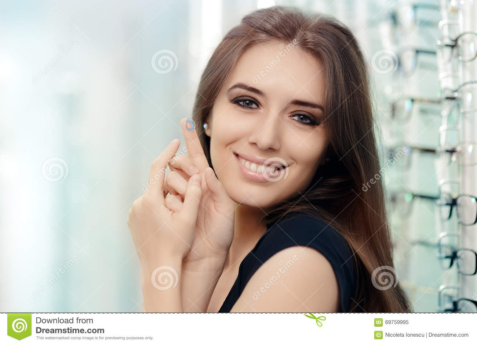 Menina bonita que guarda o recipiente da lente de contato na loja do ótico a0c98b5b0f