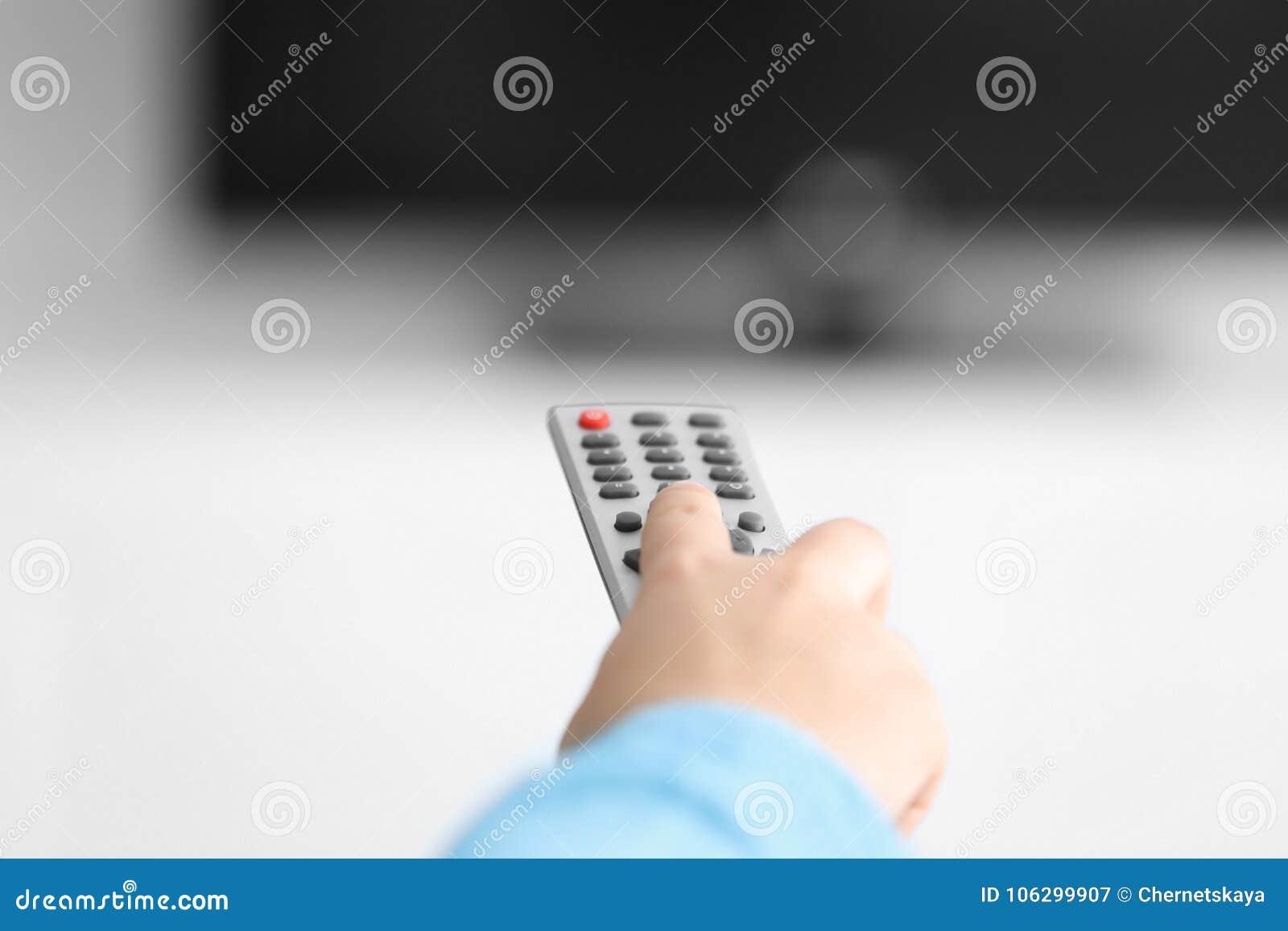 Mulher com canais de controle remoto do interruptor da tevê