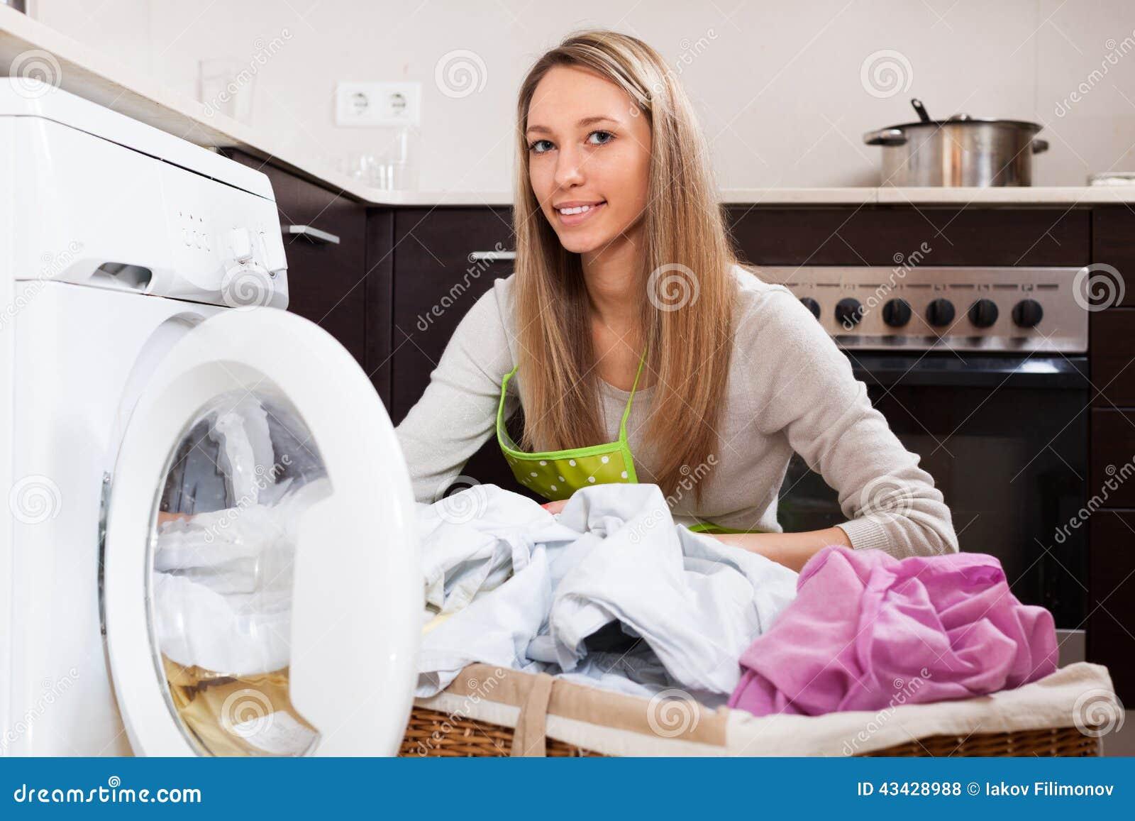 Mulher com a cesta de linho perto da máquina de lavar