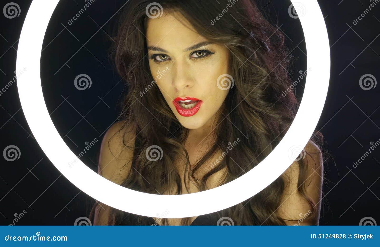 Mulher com composição desarrumado atrás do círculo fluorescente