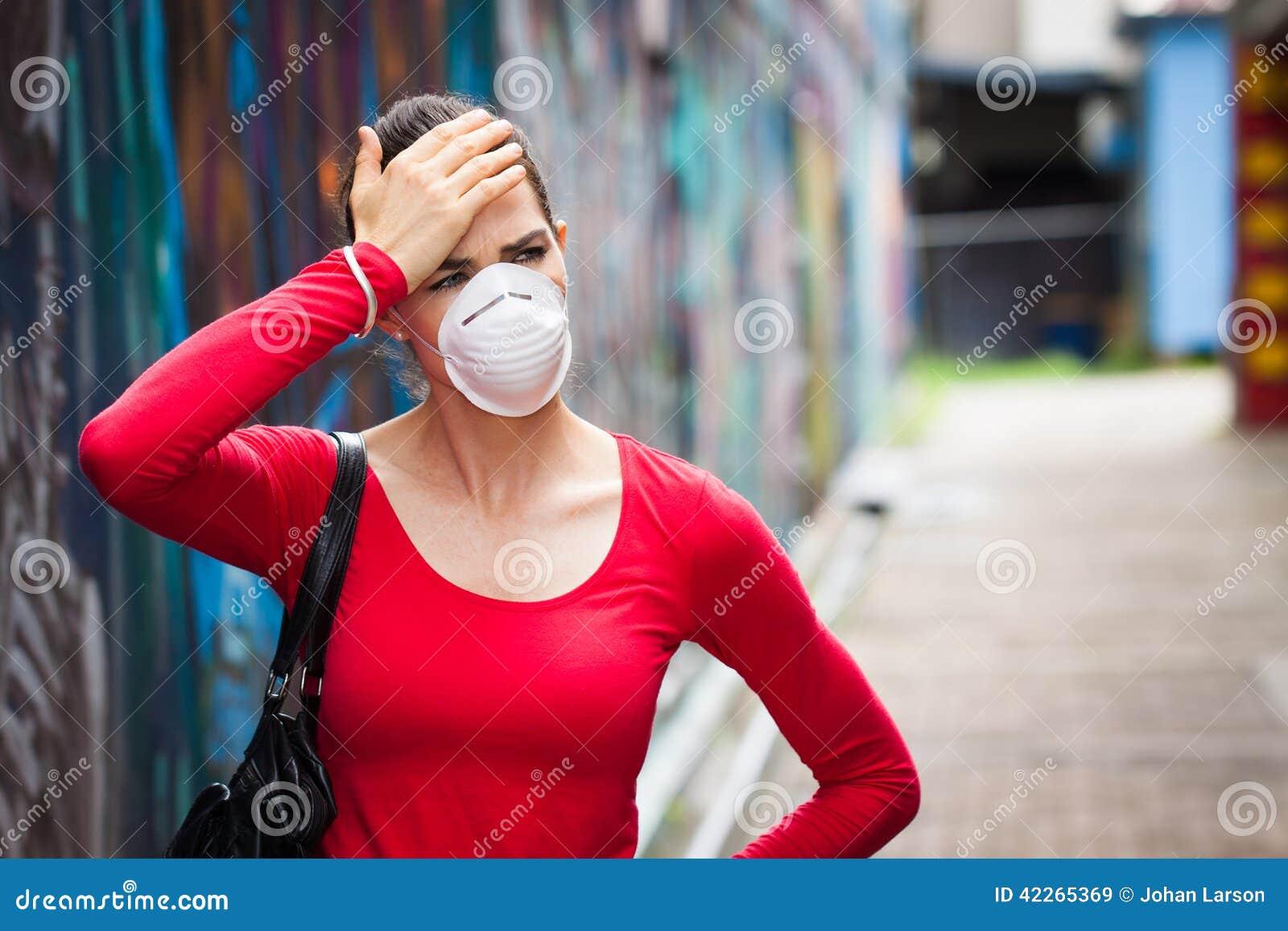 Mulher com a dor de cabeça que veste uma máscara protetora