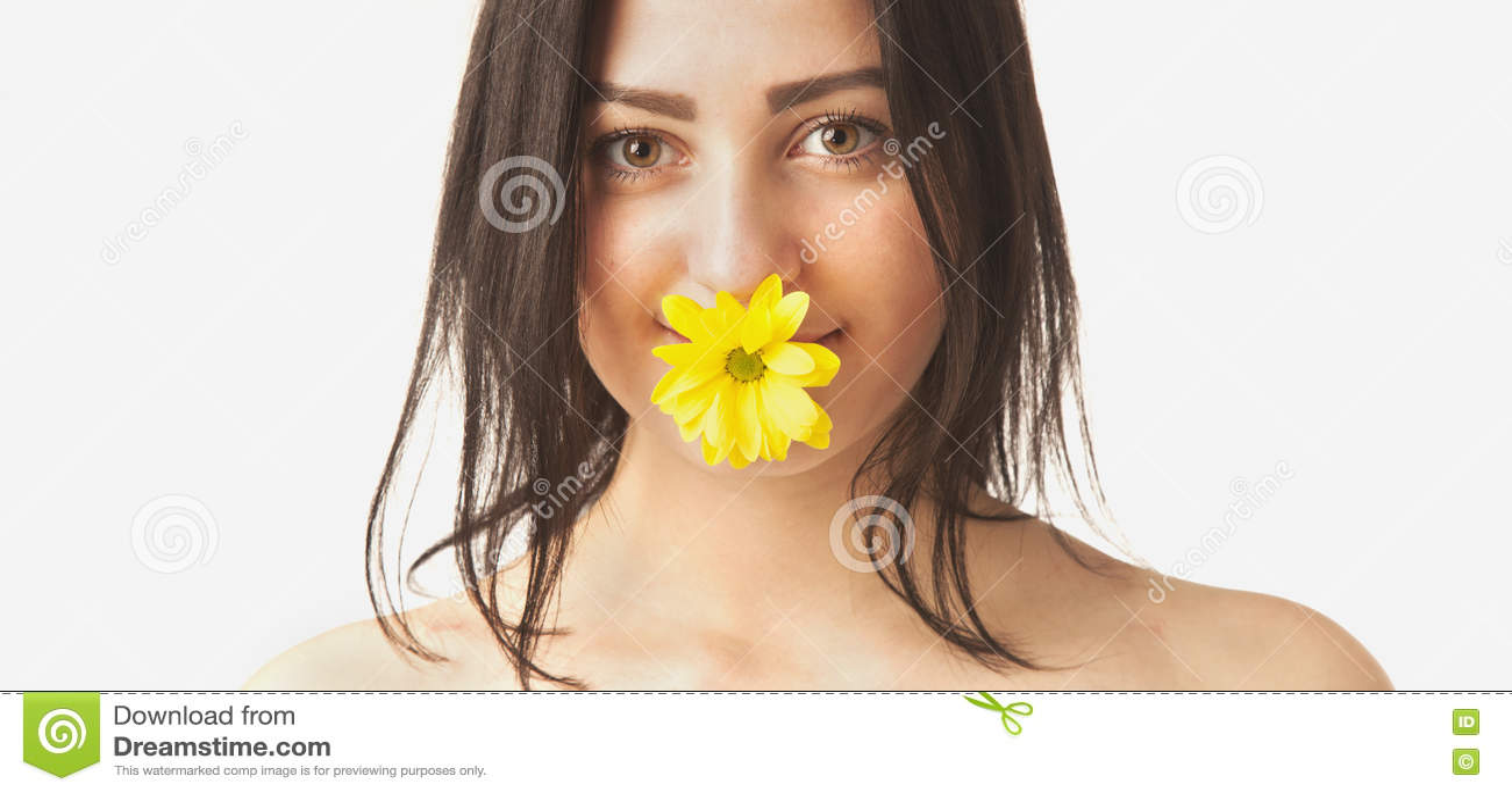 Mulher com a flor amarela em sua boca