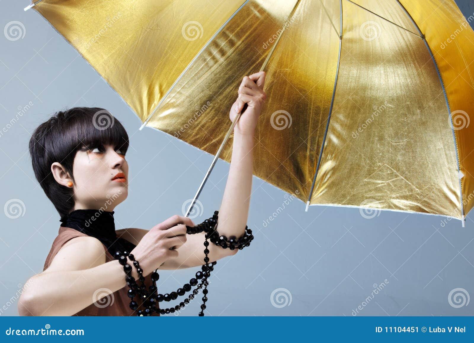 Mulher com guarda-chuva do ouro.