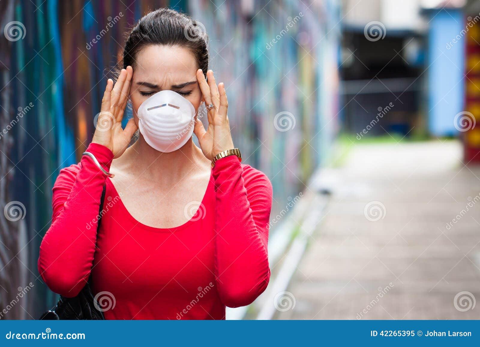 Mulher com máscara protetora vestindo da dor de cabeça