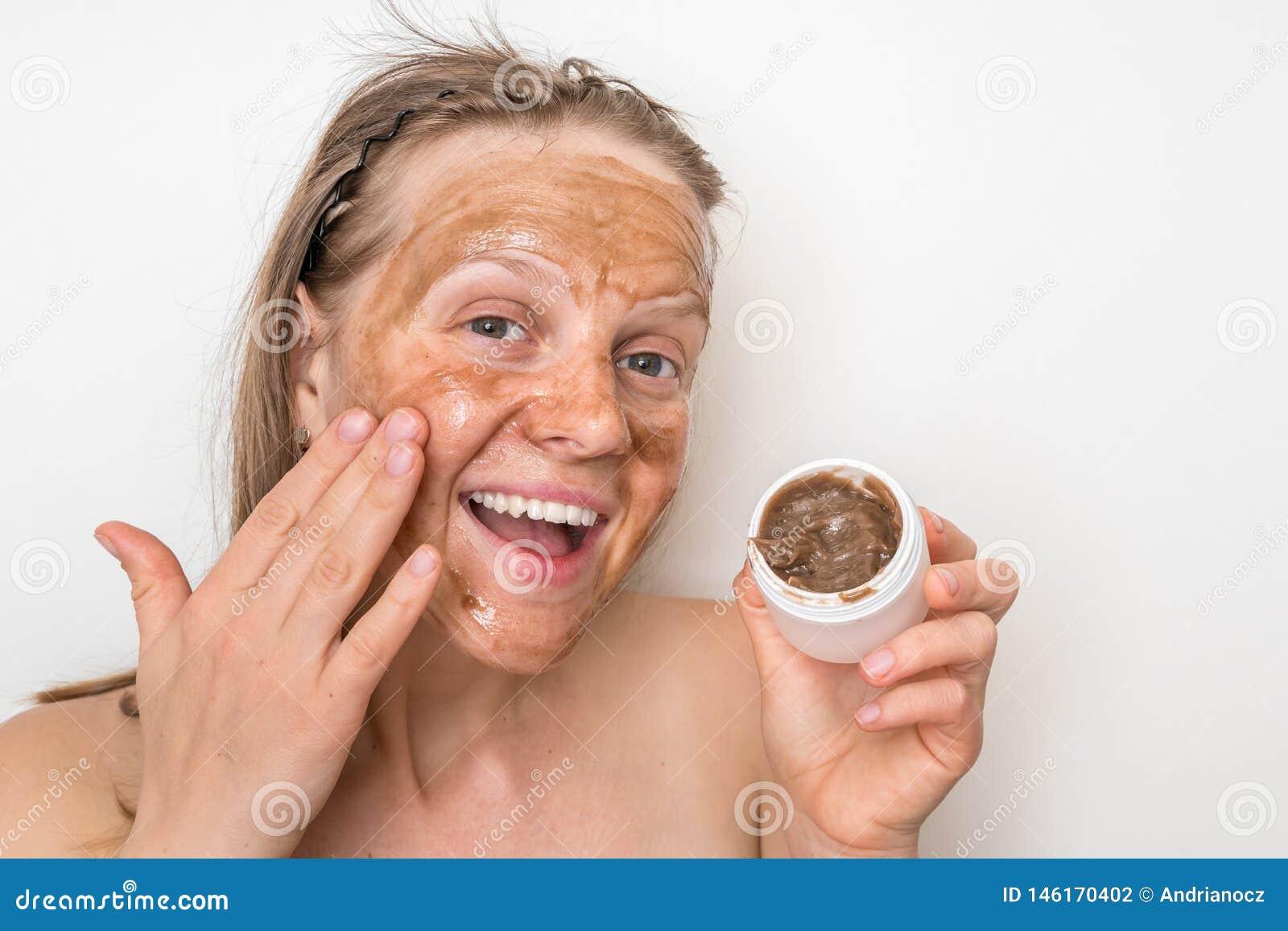 Mulher com máscara vulcânica marrom em sua cara