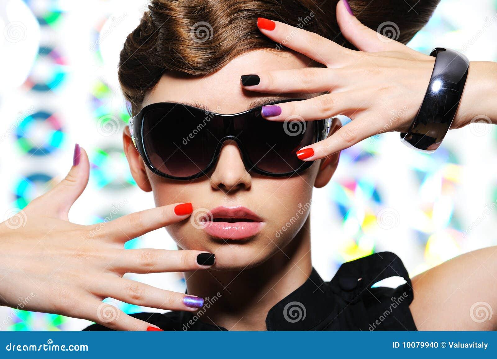Mulher com manicure da forma e os óculos de sol à moda