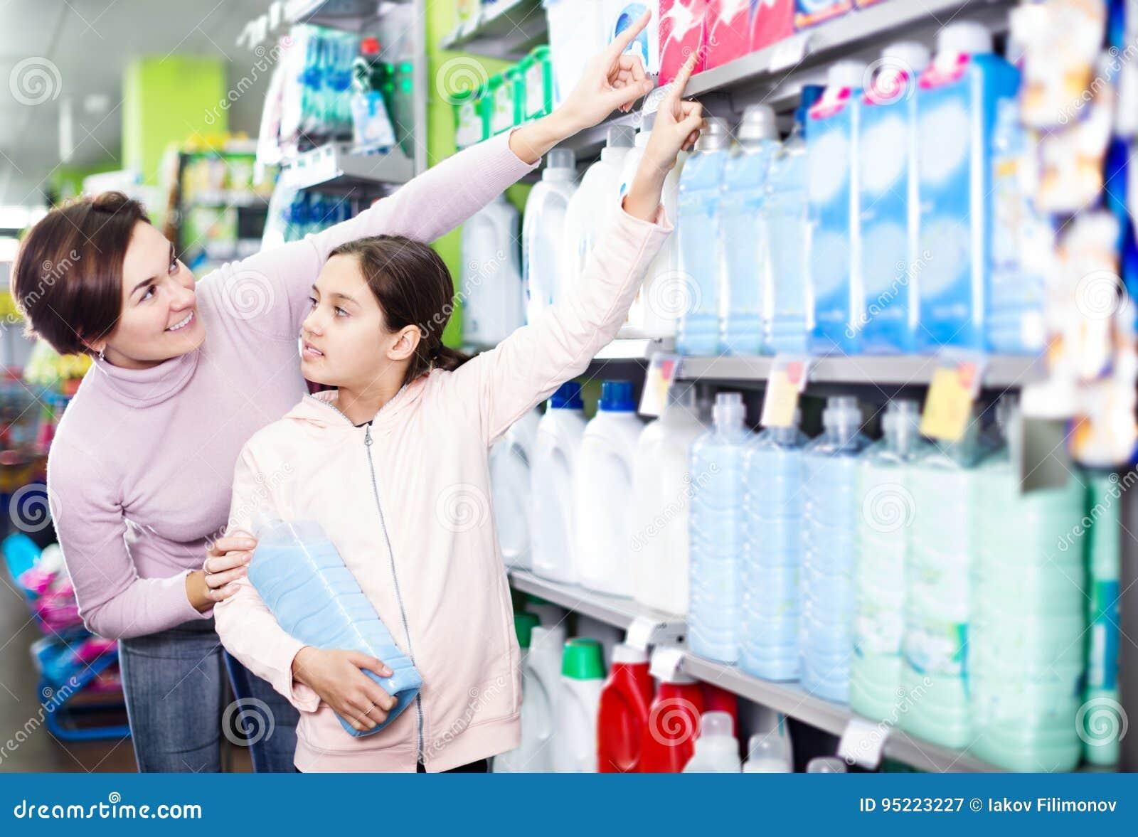 33259d97f Cliente das jovens mulheres com a procura da menina líquidos de limpeza  para a casa no supermercado Foco na criança