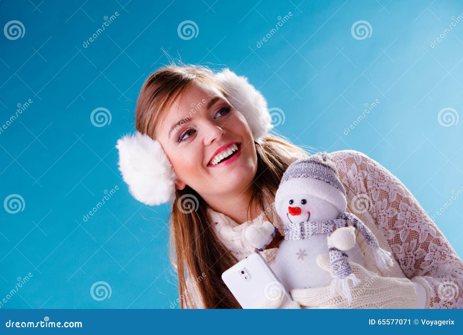Mulher com o boneco de neve pequeno que toma a foto do selfie