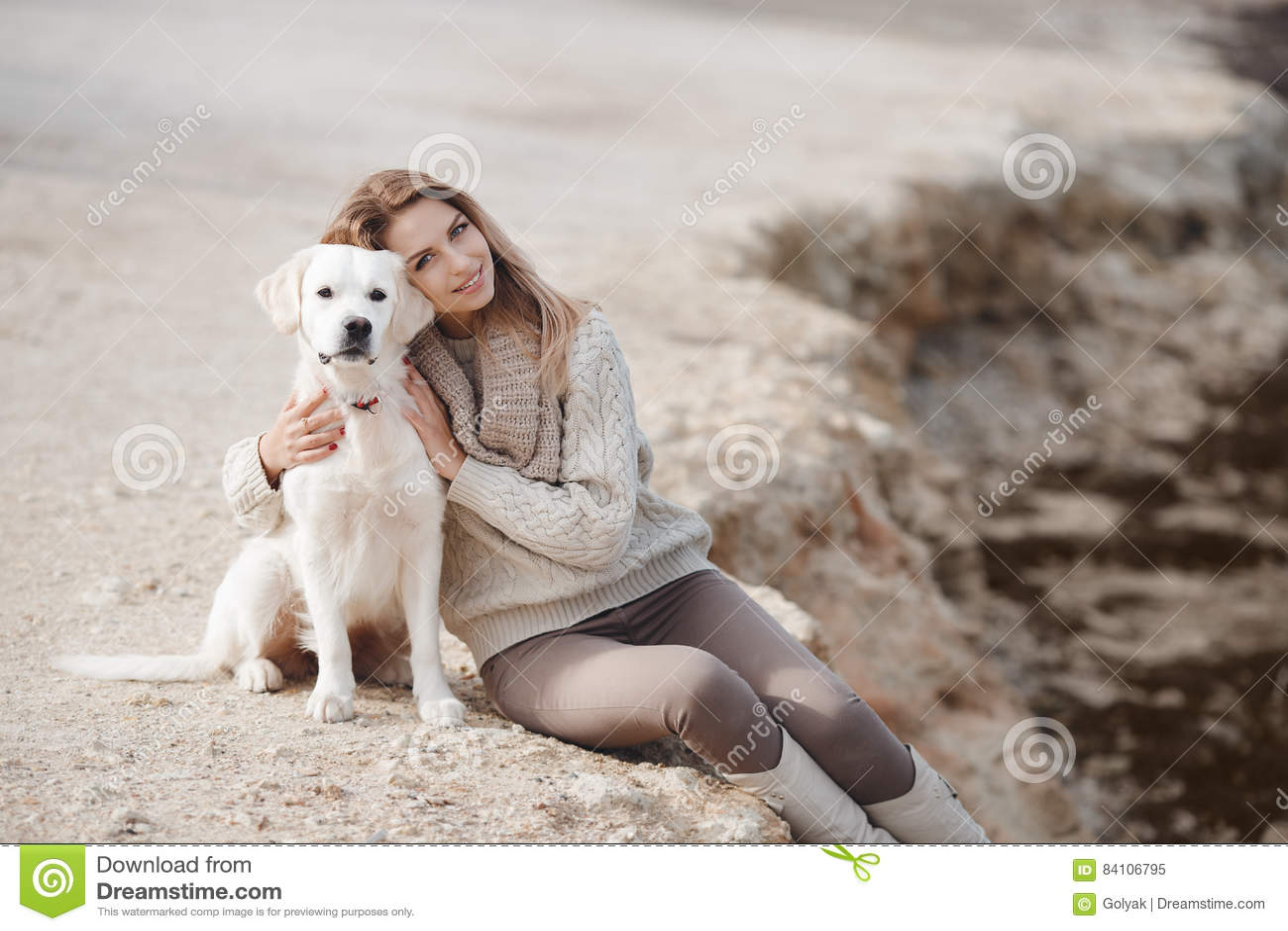 Mulher com o cão na costa de mar