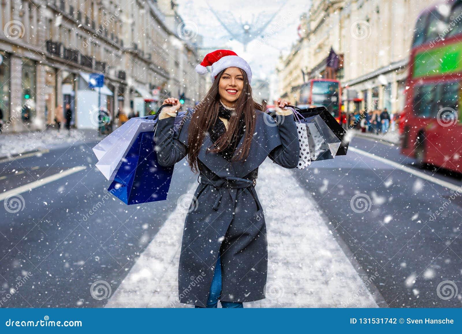 Compra do inverno no conceito de Londres  mulher de compra da cidade nova  com o chapéu vermelho de Santa e os muitos sacos de compras em Regent  Street em ... 0f407d588ec