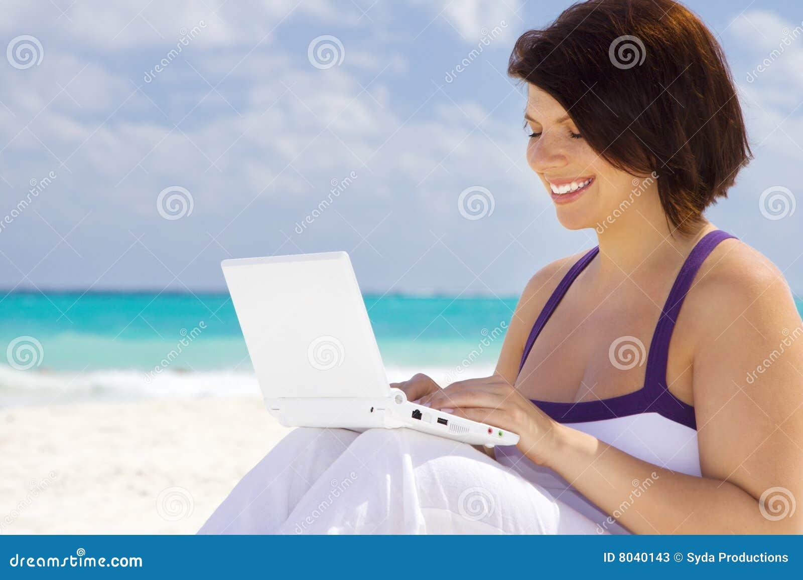 Mulher com o computador portátil na praia