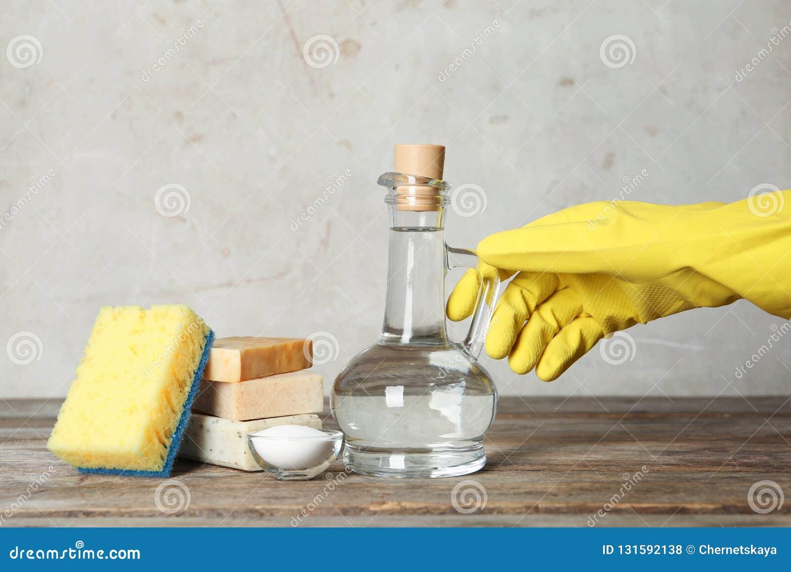 Mulher com o jarro de fontes do vinagre e de limpeza
