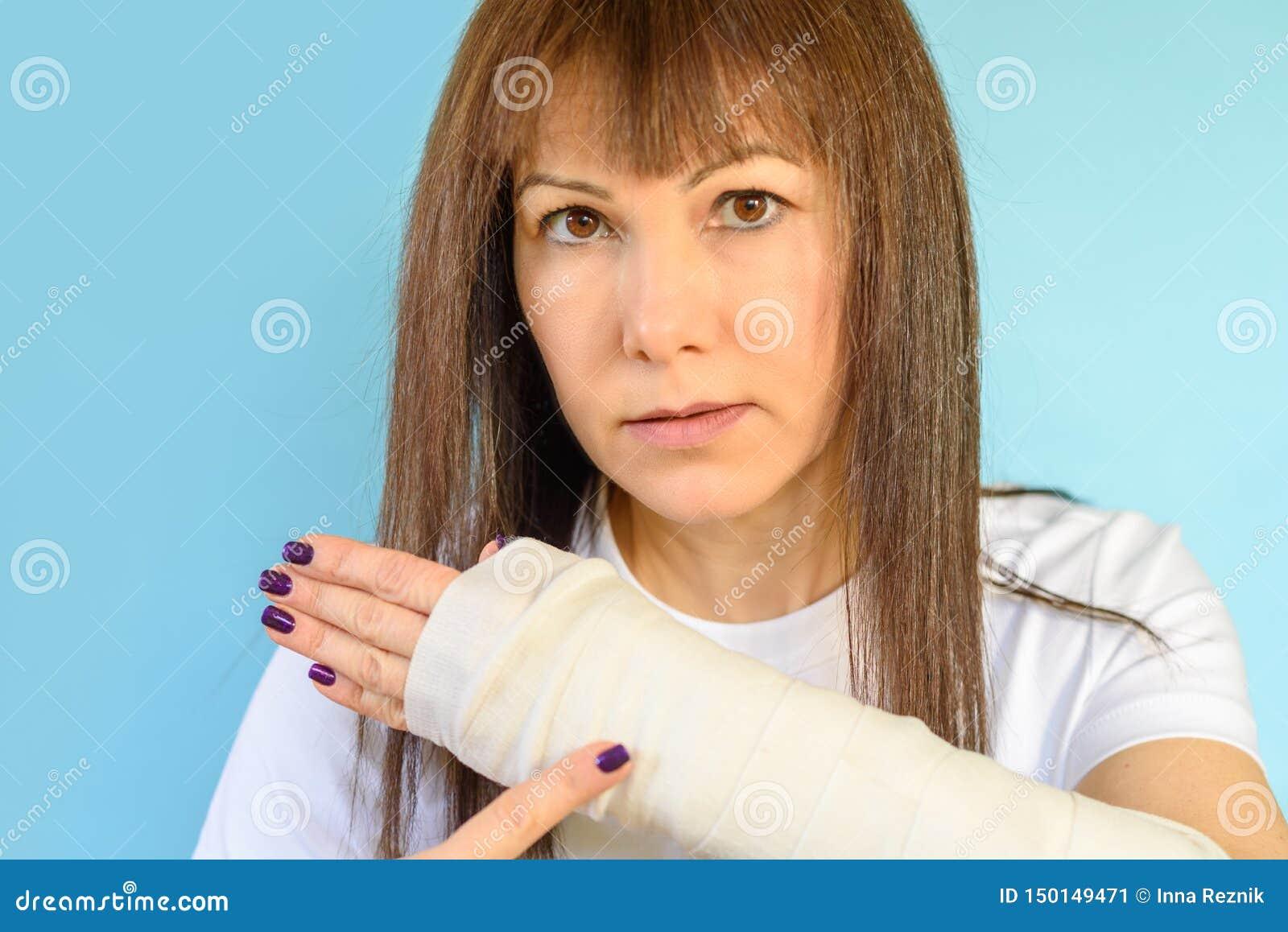 Mulher com o osso de braço quebrado no molde, mão emplastrada no fundo azul