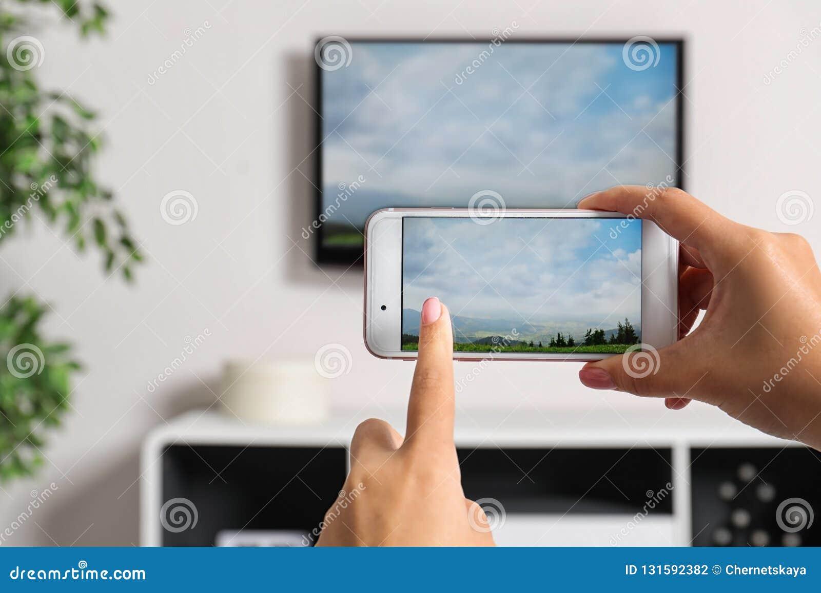 Mulher com o smartphone conectado ao aparelho de televisão