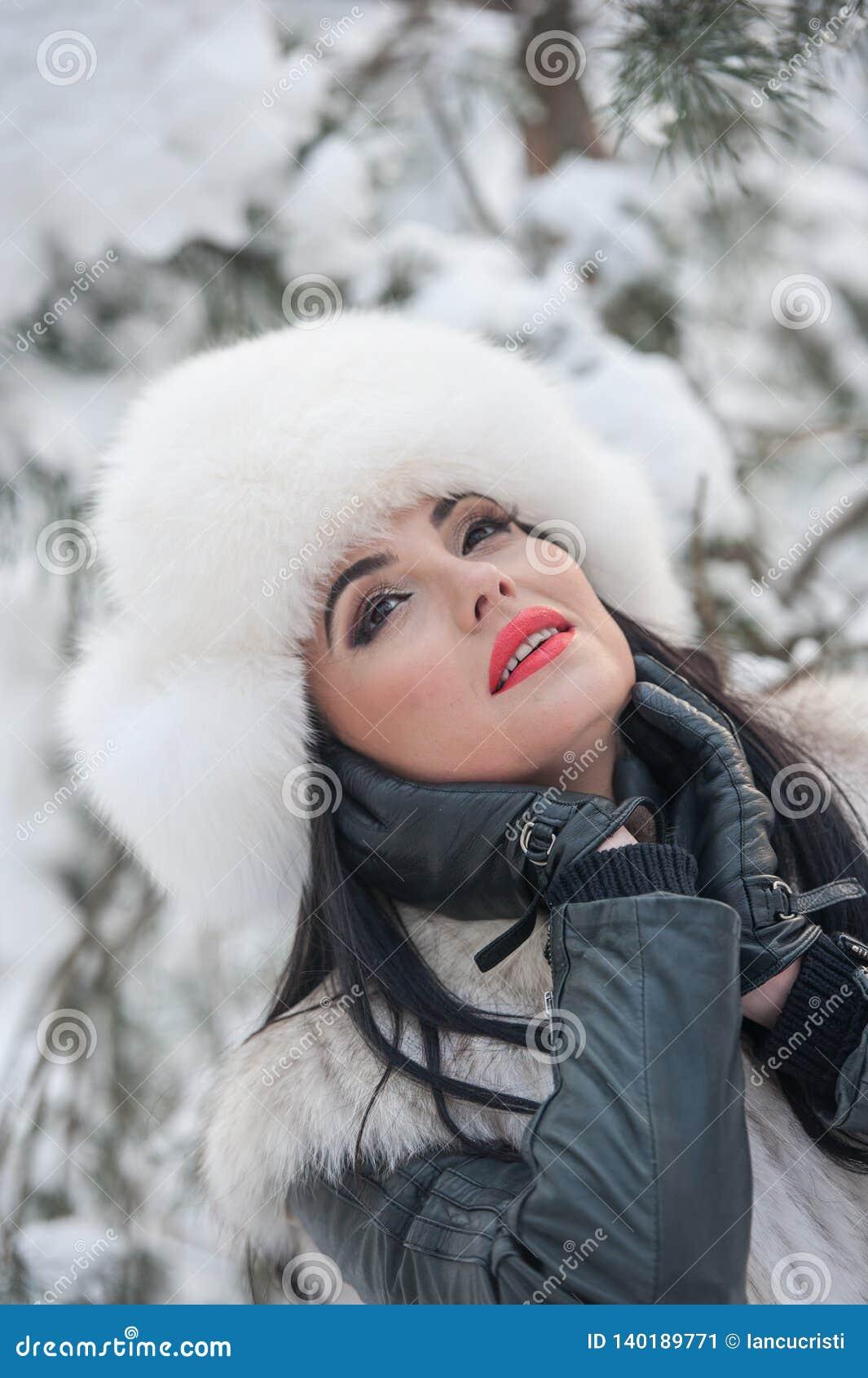 Mulher com o tampão e o waistcoat brancos da pele que aprecia o cenário do inverno perto de uma cerca do ferro Levantamento moren