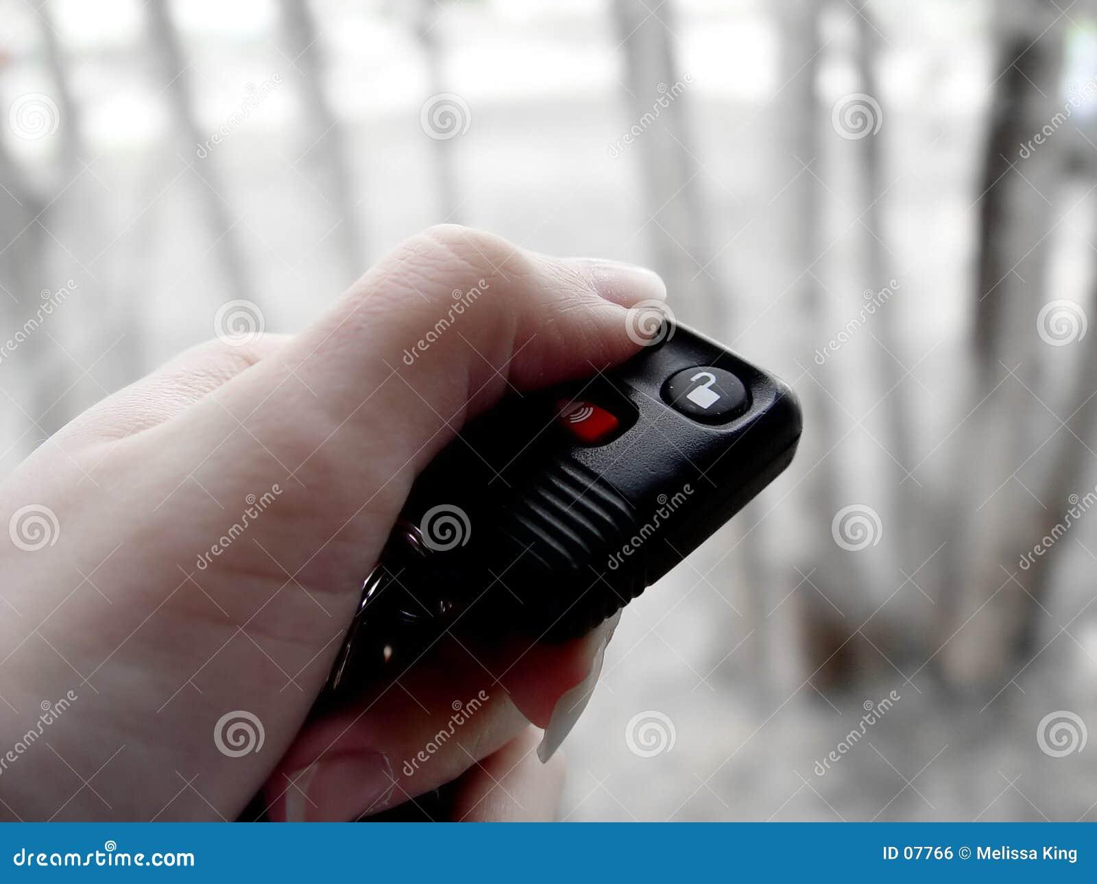 Mulher com o telecontrole do fechamento do carro