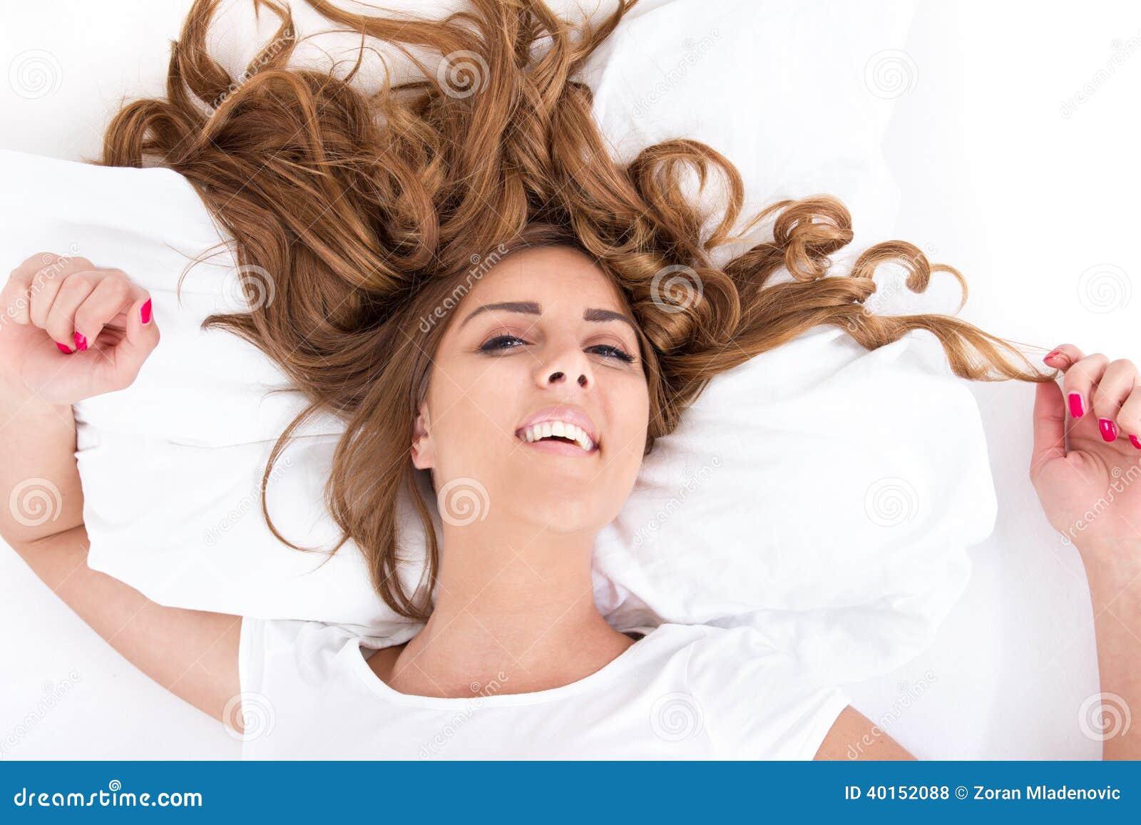 A mulher com olhos abre e o cabelo espalhou na cama na imagem brilhante