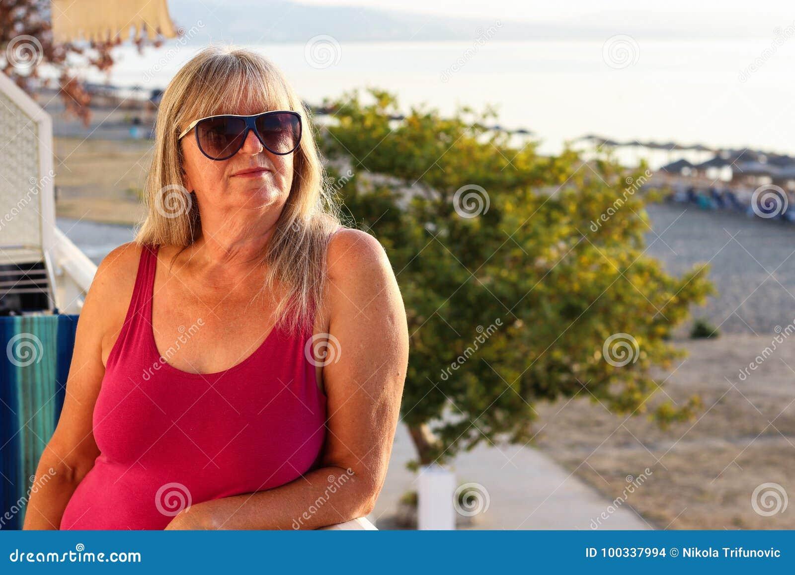 Mulher com os óculos de sol que estão no balcão cedo no Morni