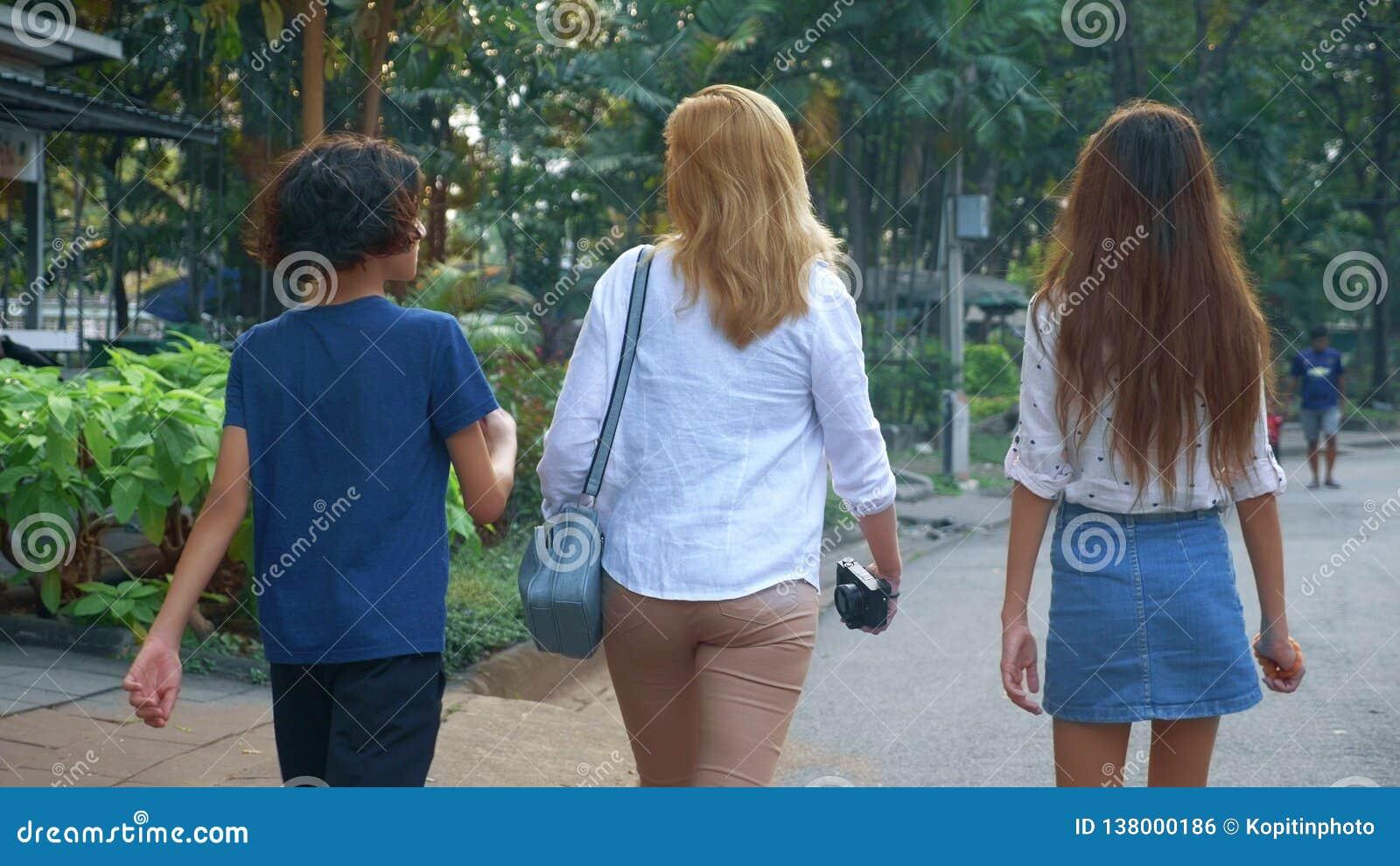 A mulher com os adolescentes das crianças, do filho e da filha com uma câmera anda através das ruas de uma grande cidade moderna
