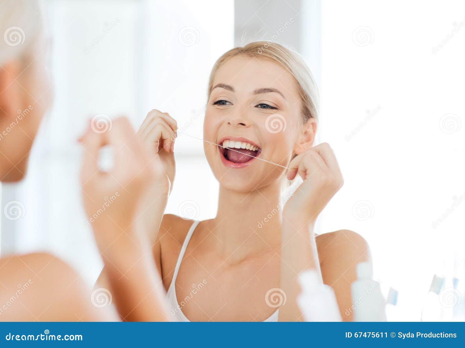 571a30eb8 Mulher Com Os Dentes Da Limpeza De Fio Dental No Banheiro Imagem de ...
