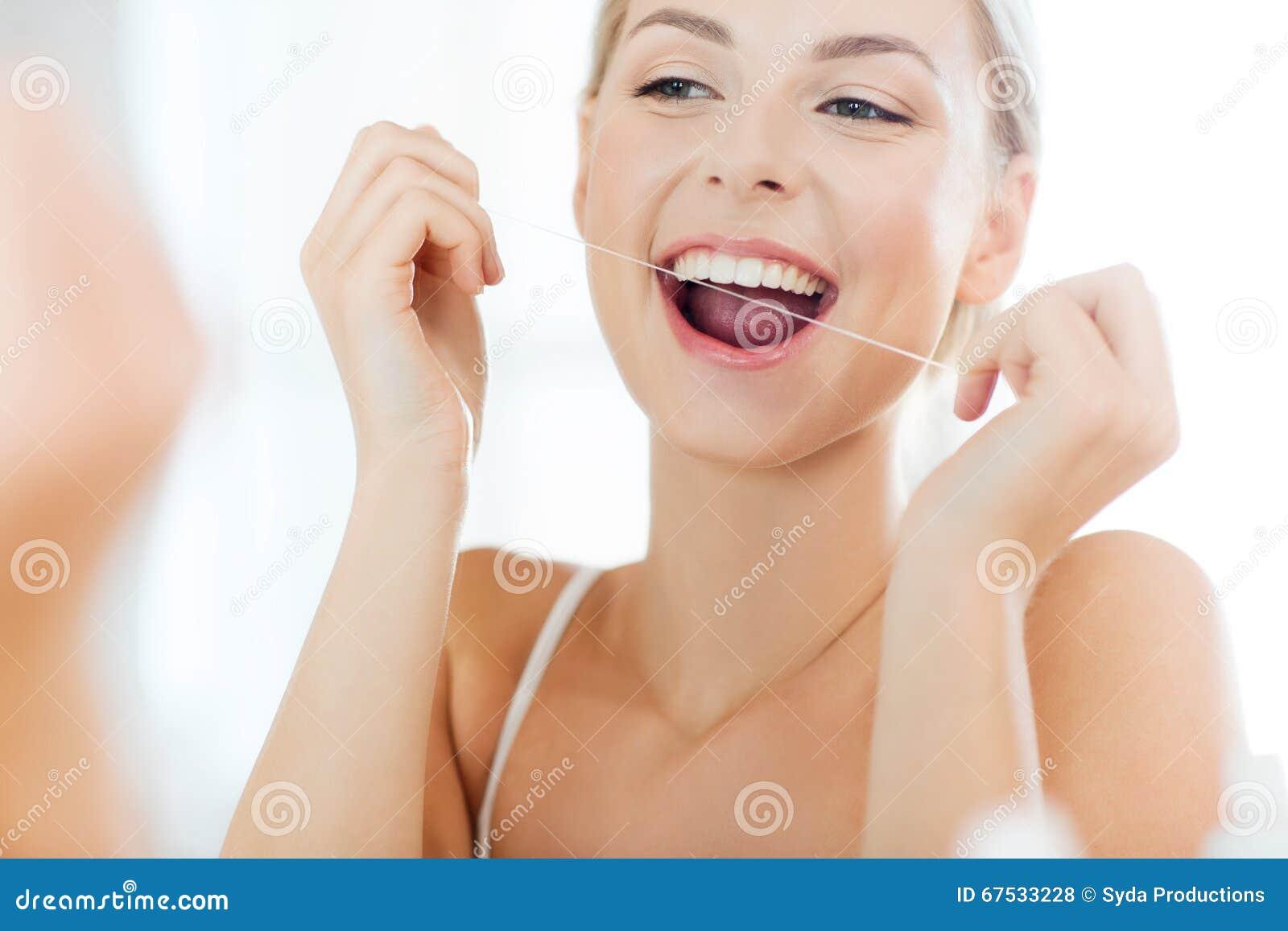 28b2bbeb0 Mulher Com Os Dentes Da Limpeza De Fio Dental No Banheiro Foto de ...